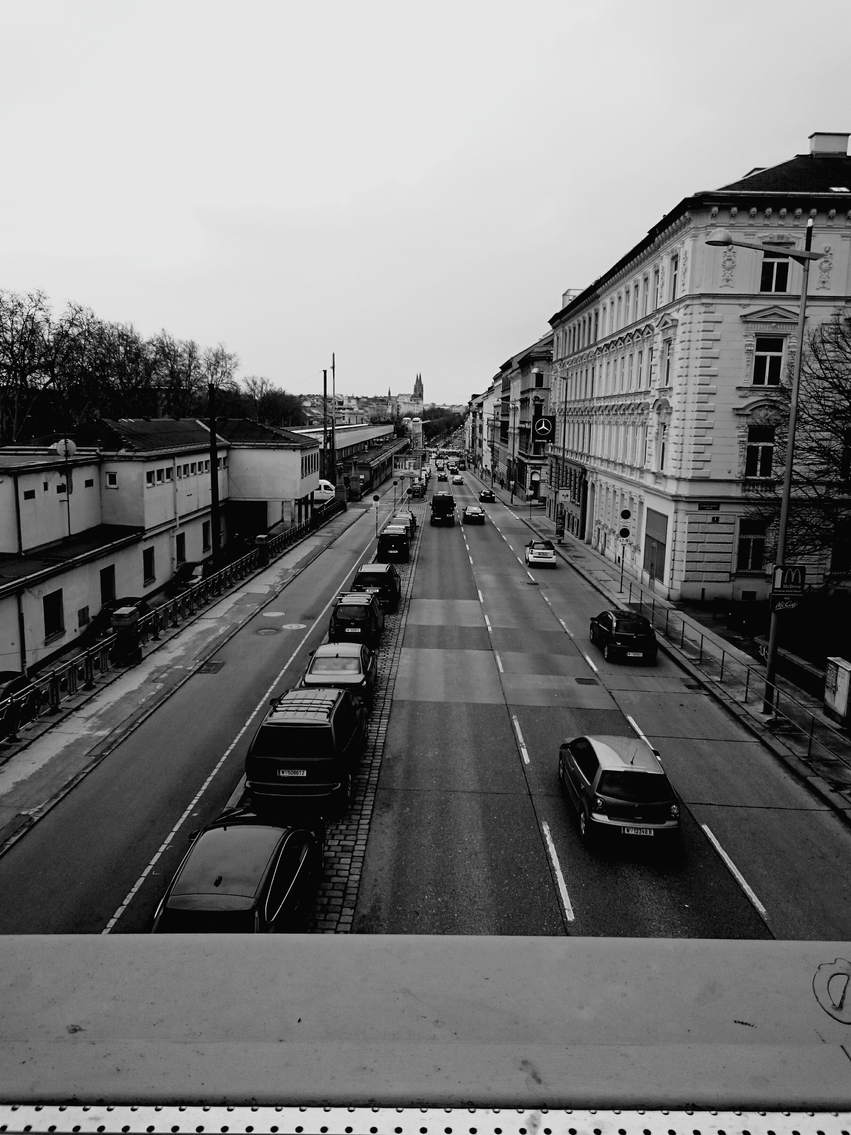 building exterior, architecture, built structure, transportation, city, car, mode of transport, the way forward, street, land vehicle, diminishing perspective, road, clear sky, incidental people, high angle view, sky, vanishing point, city life, building, road marking