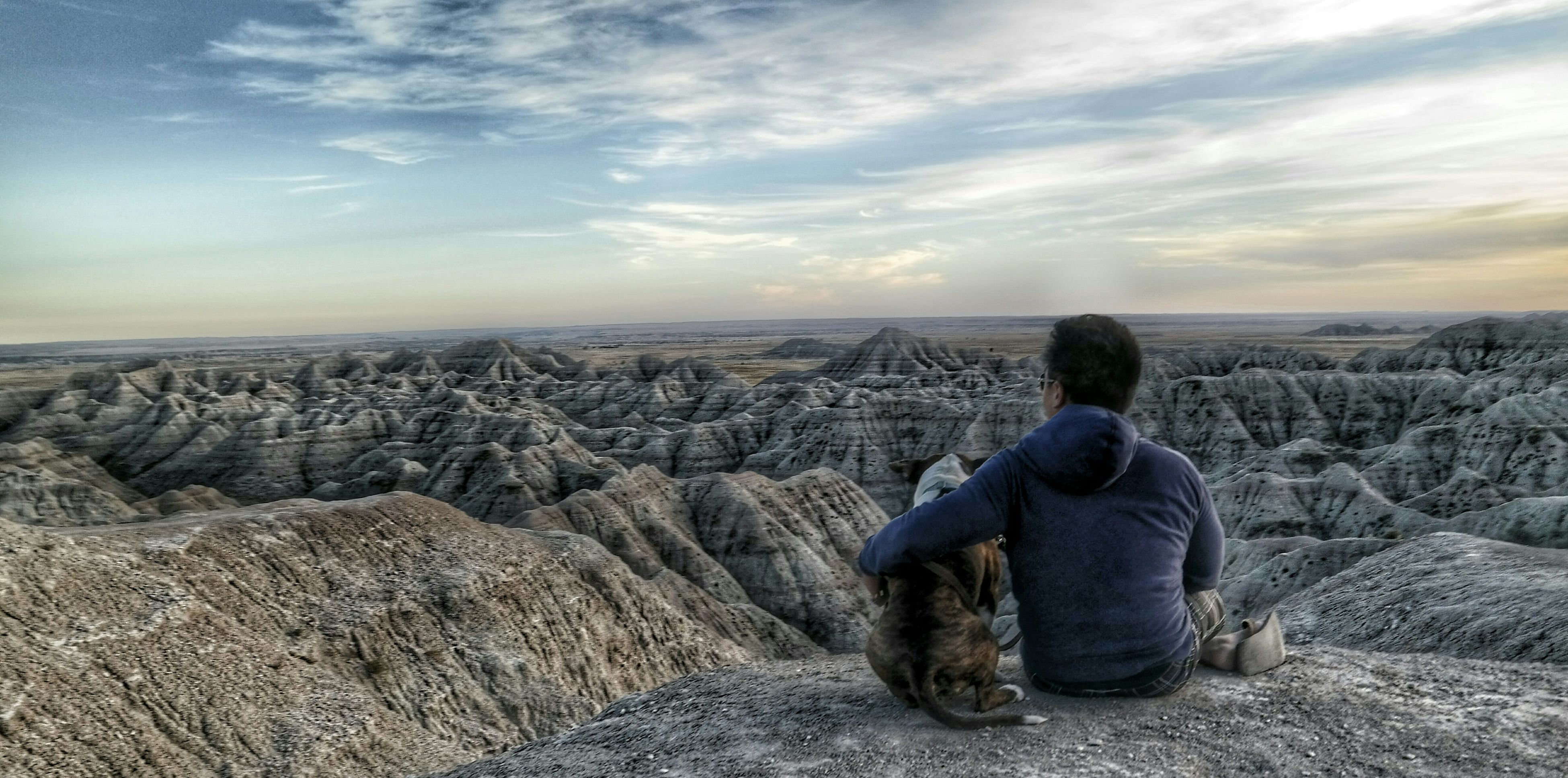 sky, men, lifestyles, rear view, leisure activity, rock - object, cloud - sky, sitting, togetherness, looking at view, scenics, person, nature, tranquility, full length, beauty in nature, landscape, tranquil scene