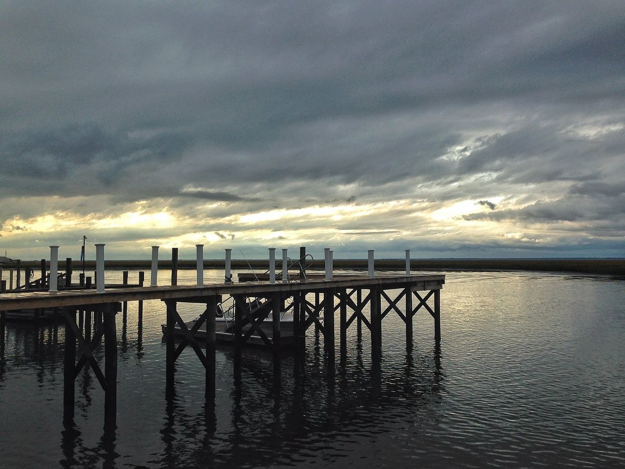 Pier Over River Against Cloudy Sky At Dusk