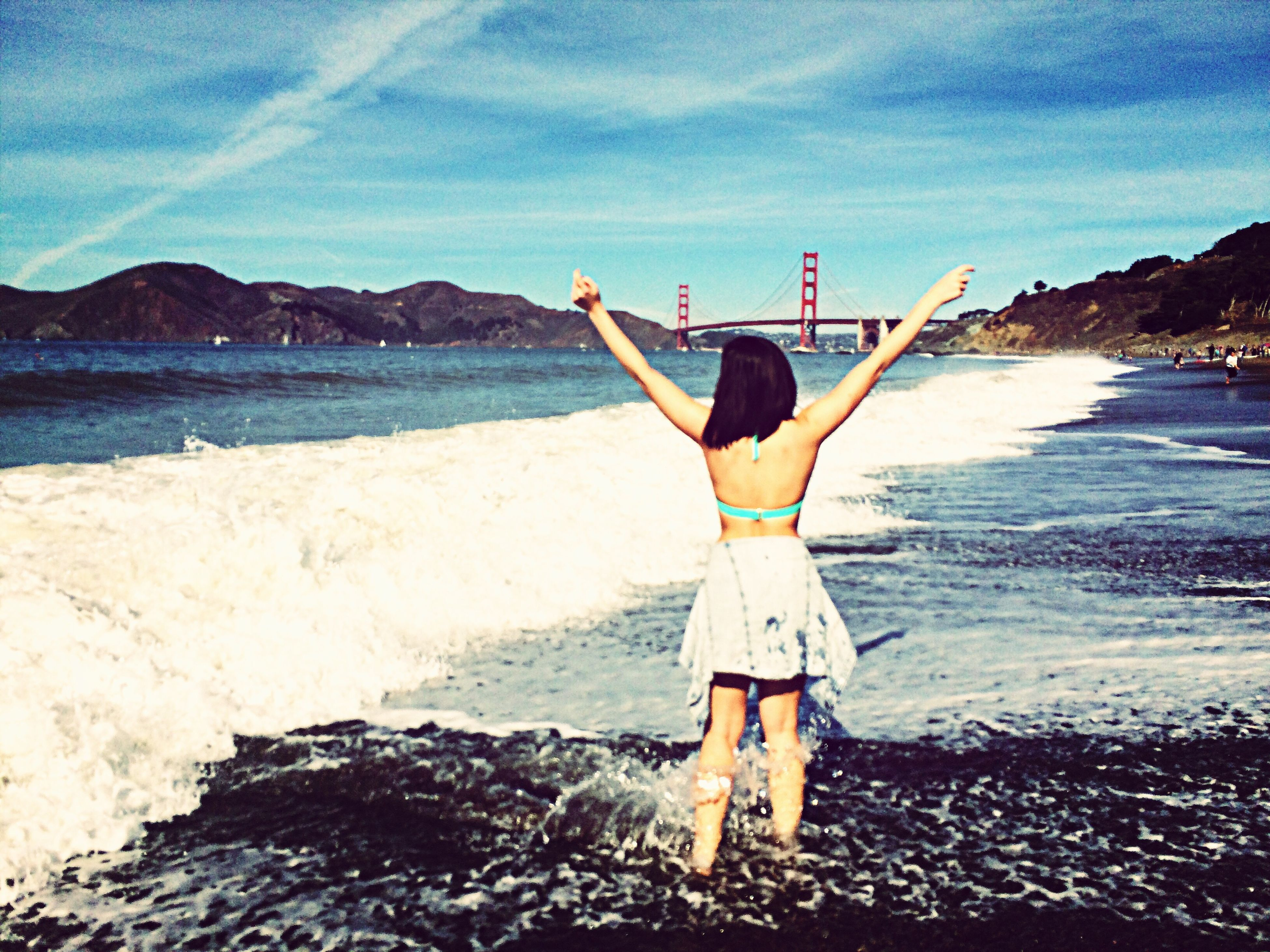 water, sea, full length, lifestyles, sky, leisure activity, young adult, standing, beach, young women, shore, casual clothing, scenics, vacations, arms outstretched, tranquil scene, rear view, tranquility