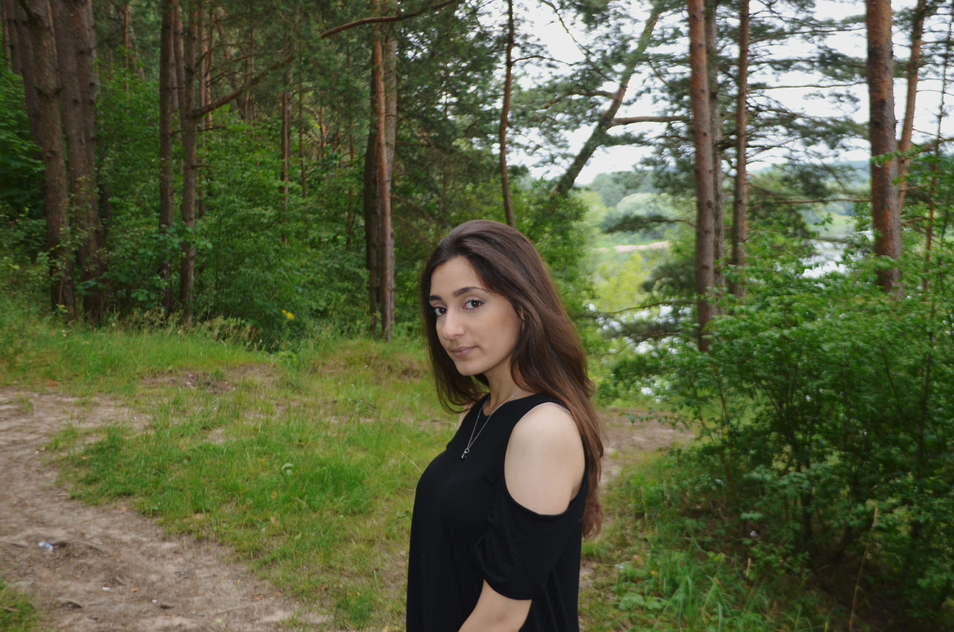 young adult, real people, young women, one person, leisure activity, standing, tree, lifestyles, nature, beautiful woman, outdoors, forest, looking at camera, day, portrait, people