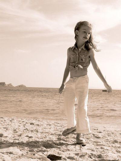 Beach Sea Childhood One Person Real People Sand Water Front View Sky Elementary Age Full Length Leisure Activity Standing Girls Outdoors Day Nature Horizon Over Water Children Only People Summertime Play Sepia
