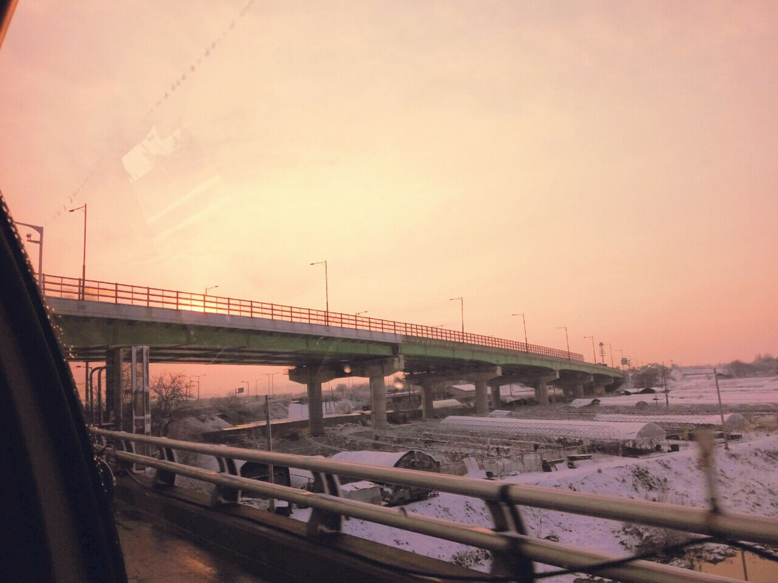connection, bridge - man made structure, sunset, transportation, railing, built structure, water, architecture, bridge, sky, clear sky, sun, sea, river, orange color, nature, engineering, outdoors, mode of transport, sunlight