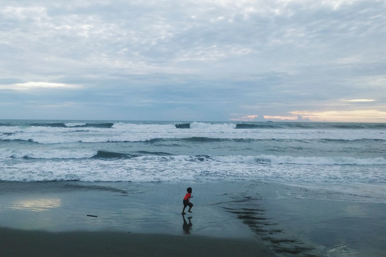 sea, beach, water, sky, nature, horizon over water, shore, scenics, beauty in nature, real people, sunset, cloud - sky, outdoors, leisure activity, wave, sand, one person, vacations, full length, standing, men, day, extreme sports, people