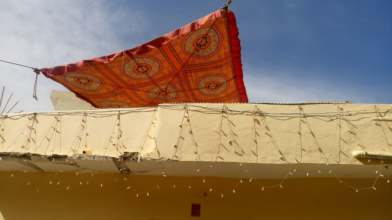 Low Angle View Of Sheet Drying Against The Sky