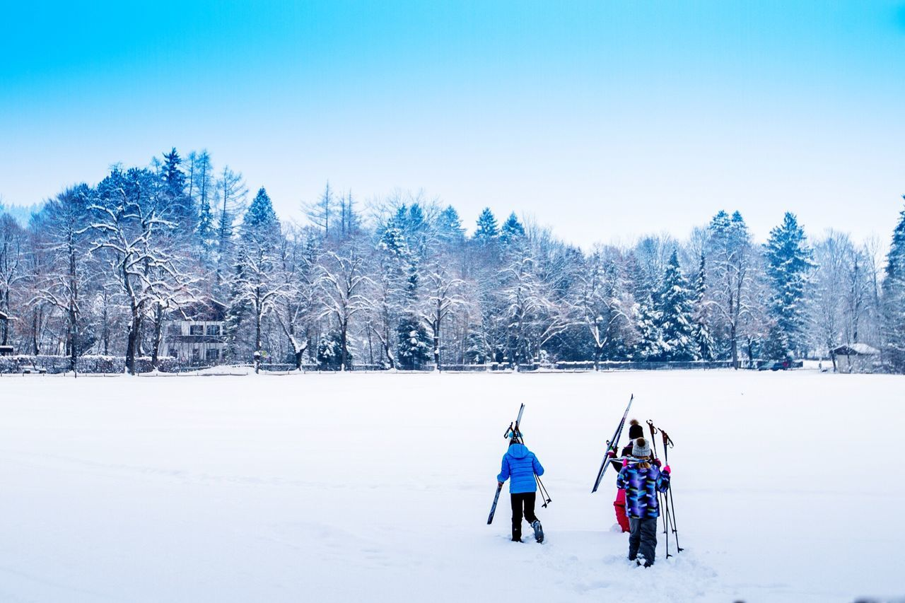 snow, winter, cold temperature, nature, beauty in nature, scenics, weather, landscape, field, tree, outdoors, tranquility, tranquil scene, frozen, day, leisure activity, real people, adventure, clear sky, full length, sport, sky, warm clothing, tobogganing