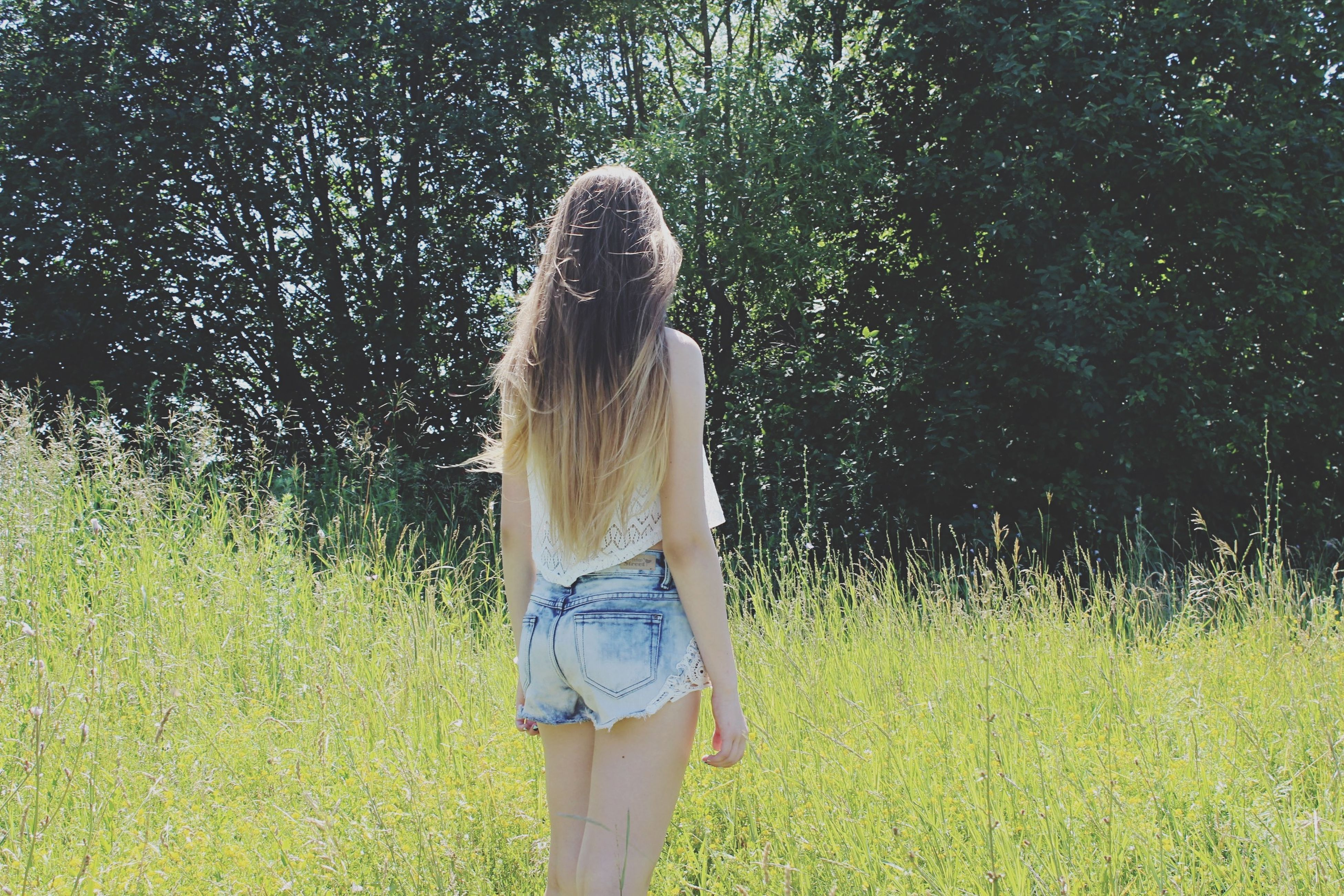 grass, lifestyles, young women, standing, leisure activity, long hair, casual clothing, full length, young adult, field, three quarter length, rear view, tree, person, grassy, plant, nature