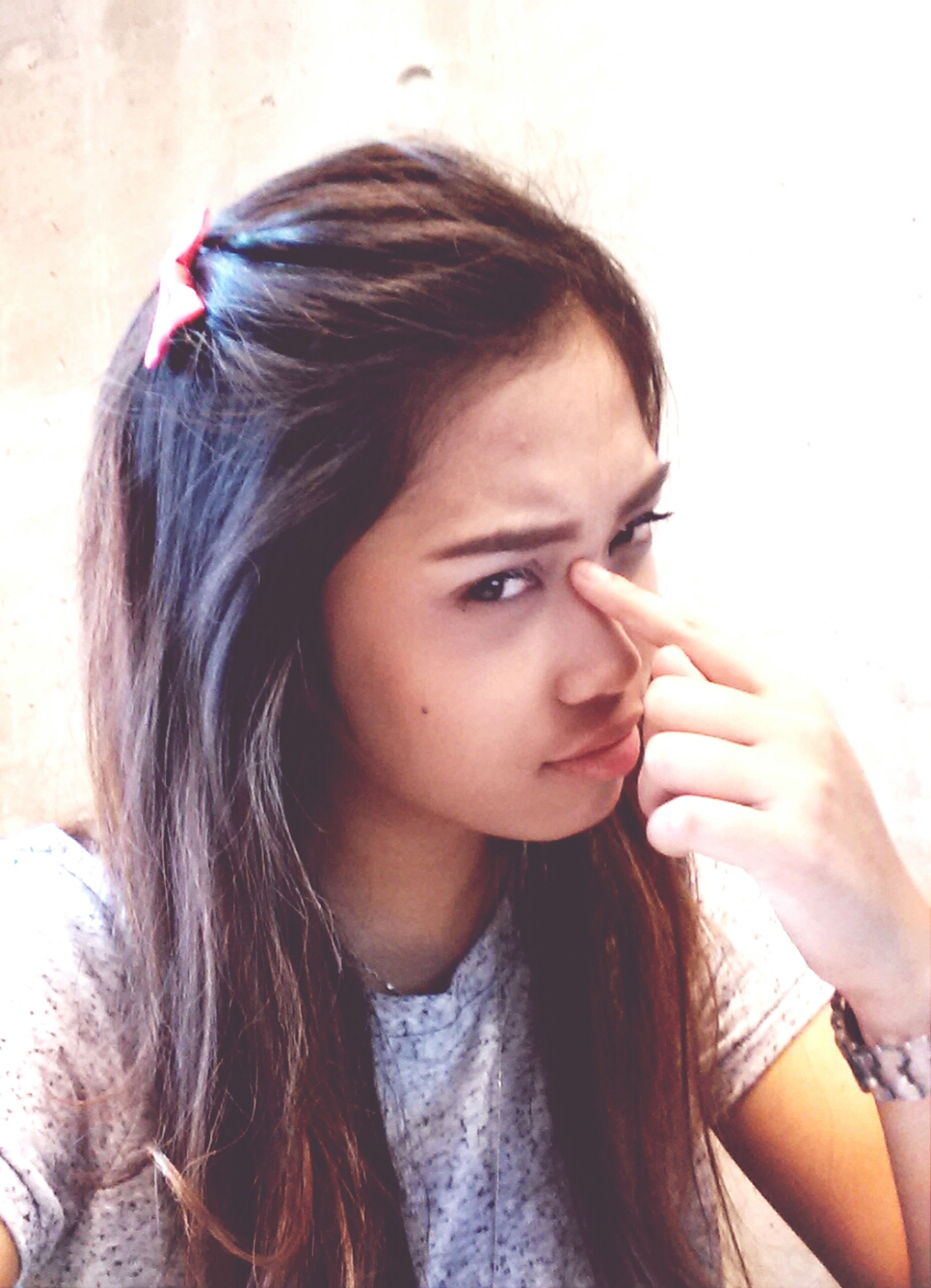 young adult, young women, indoors, headshot, person, portrait, looking at camera, lifestyles, front view, long hair, wall - building feature, close-up, human face, contemplation, black hair, head and shoulders, leisure activity