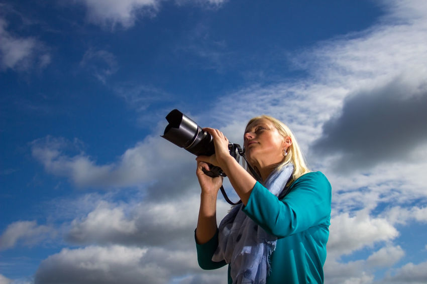 a woman with a camera on a blue sky background Autentic Moments Backgrounds Beautiful Woman Beauty Blond Hair Blue Cloud - Sky EyeEmNewHere Home Video Camera One Person One Woman Only One Young Woman Only Only Women Photo Camera Photographer Photography Themes Real People Video Women Work Working Young Adult Young Women Women Around The World Long Goodbye