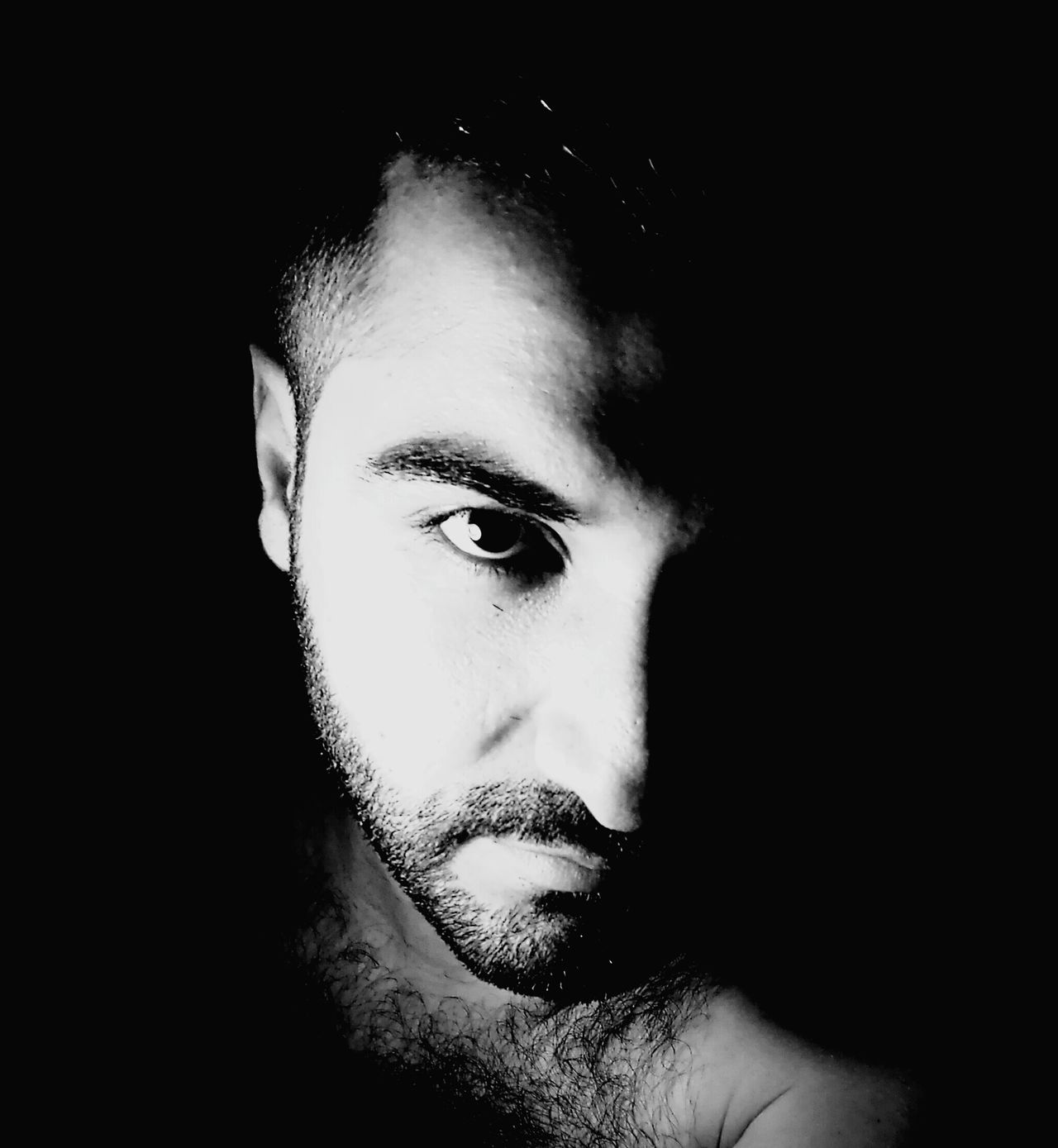 Refugee Human Face Portrait Bearded Man Black And White Young Adult Looking At Camera Black Background Close-up