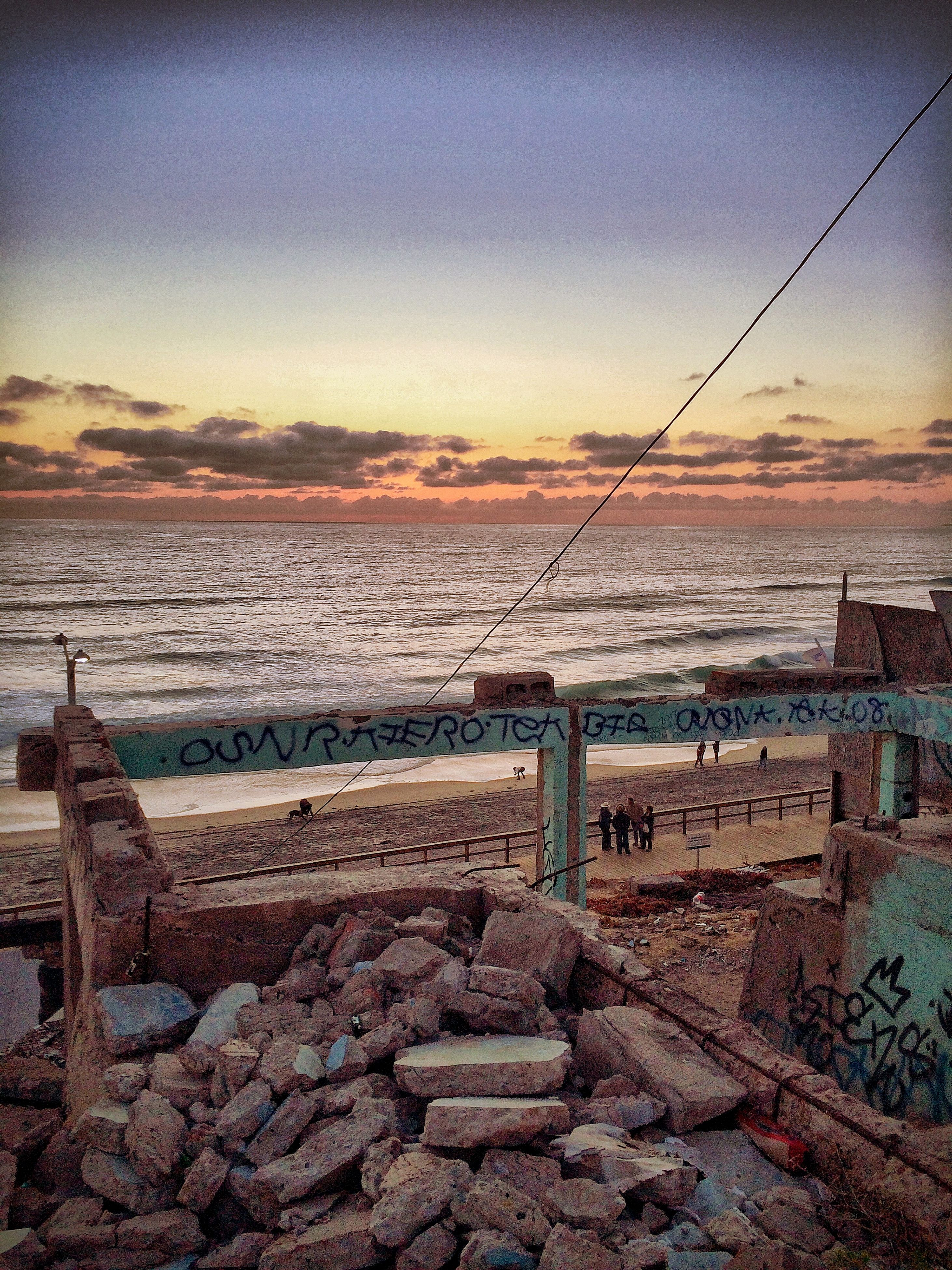 sky, sunset, tranquil scene, tranquility, water, scenics, sea, nature, beach, beauty in nature, landscape, outdoors, horizon over water, fence, no people, idyllic, sunlight, shore, remote, non-urban scene