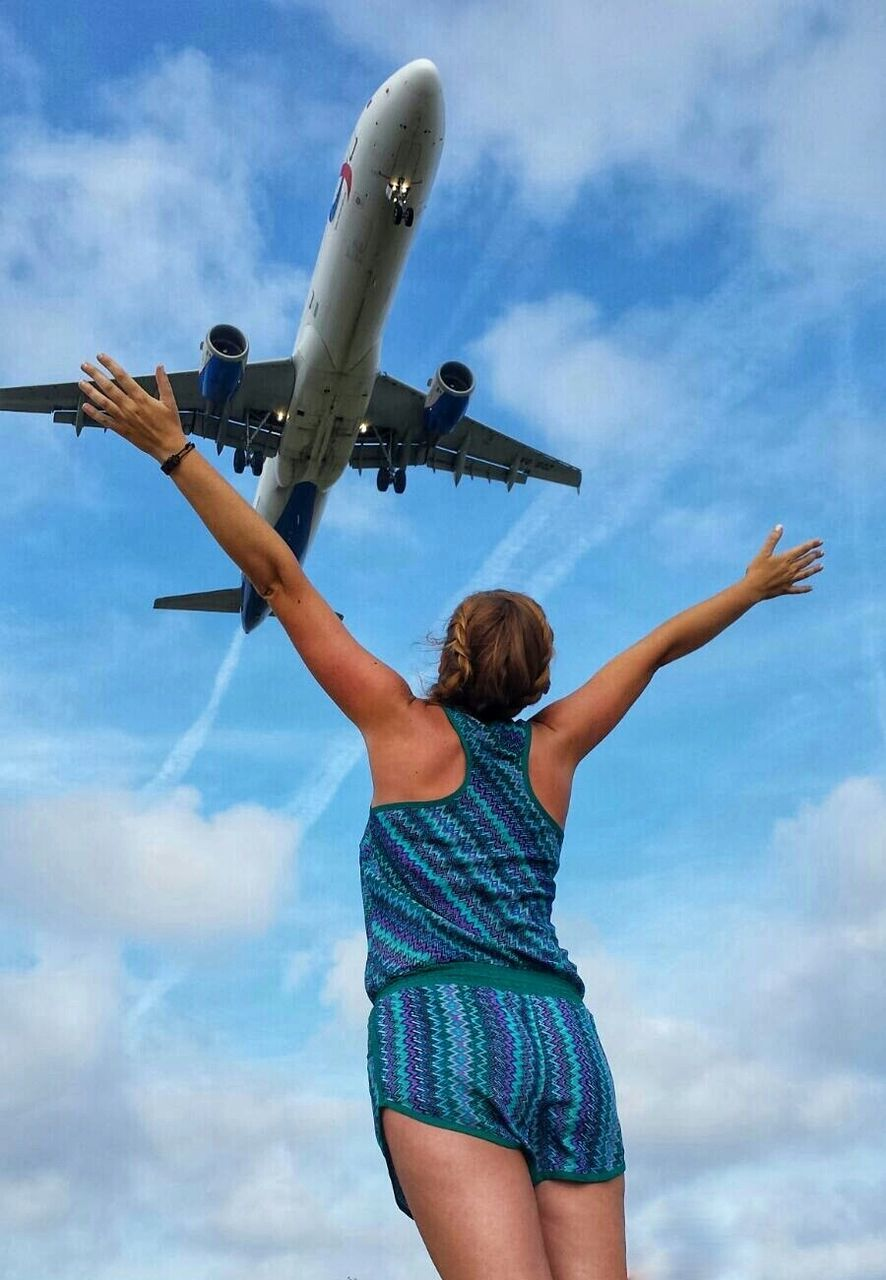 sky, rear view, cloud - sky, low angle view, one person, leisure activity, airplane, day, outdoors, standing, real people, lifestyles, young adult, women, blond hair, flying, young women, nature, adult, adults only, people