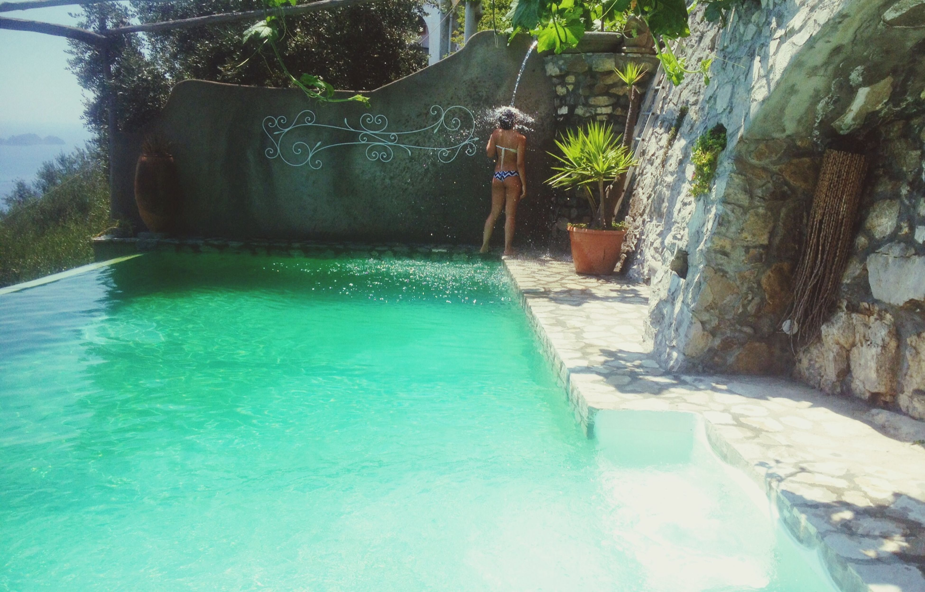 water, swimming pool, waterfront, motion, built structure, tree, building exterior, lifestyles, architecture, blue, sea, leisure activity, splashing, sunlight, day, outdoors, nature, rock - object