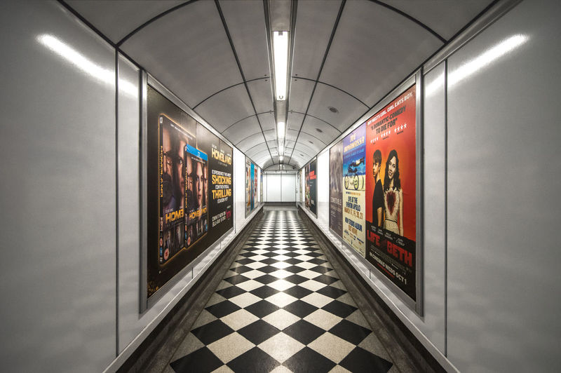 the symmetry of a tunnel in a station of the London Underground system Ad Central Line Charing Cross Checkered Ealing Jubilee Line London Poster Trafalgar Transport For London Tube Underground Westbound Carriage Cinema Eastbound England Escalator Leyton Lift Piccadilly Subway Theatre Train Tunnel