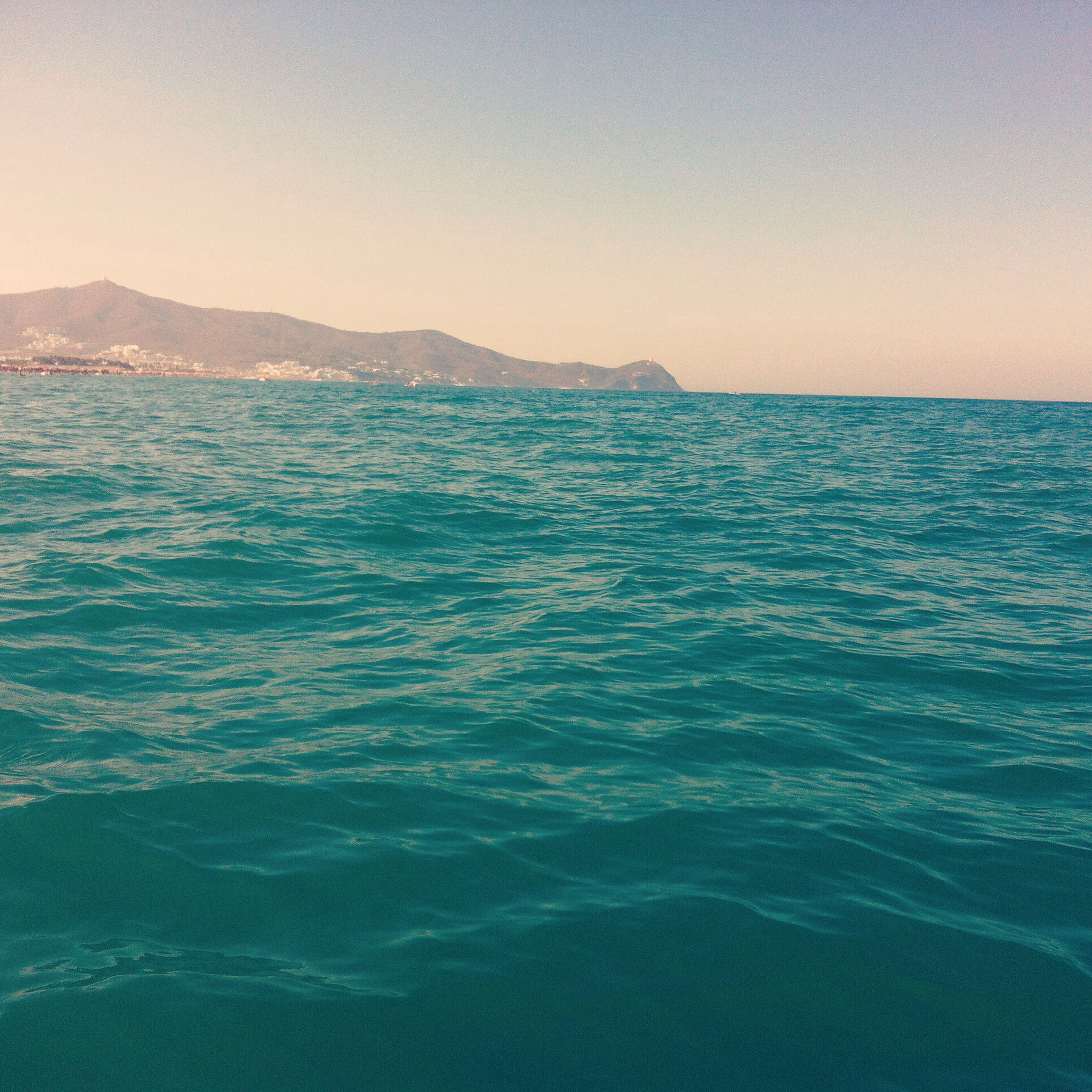 water, sea, scenics, tranquil scene, waterfront, beauty in nature, clear sky, tranquility, rippled, blue, nature, copy space, idyllic, seascape, mountain, horizon over water, outdoors, remote, wave, sky