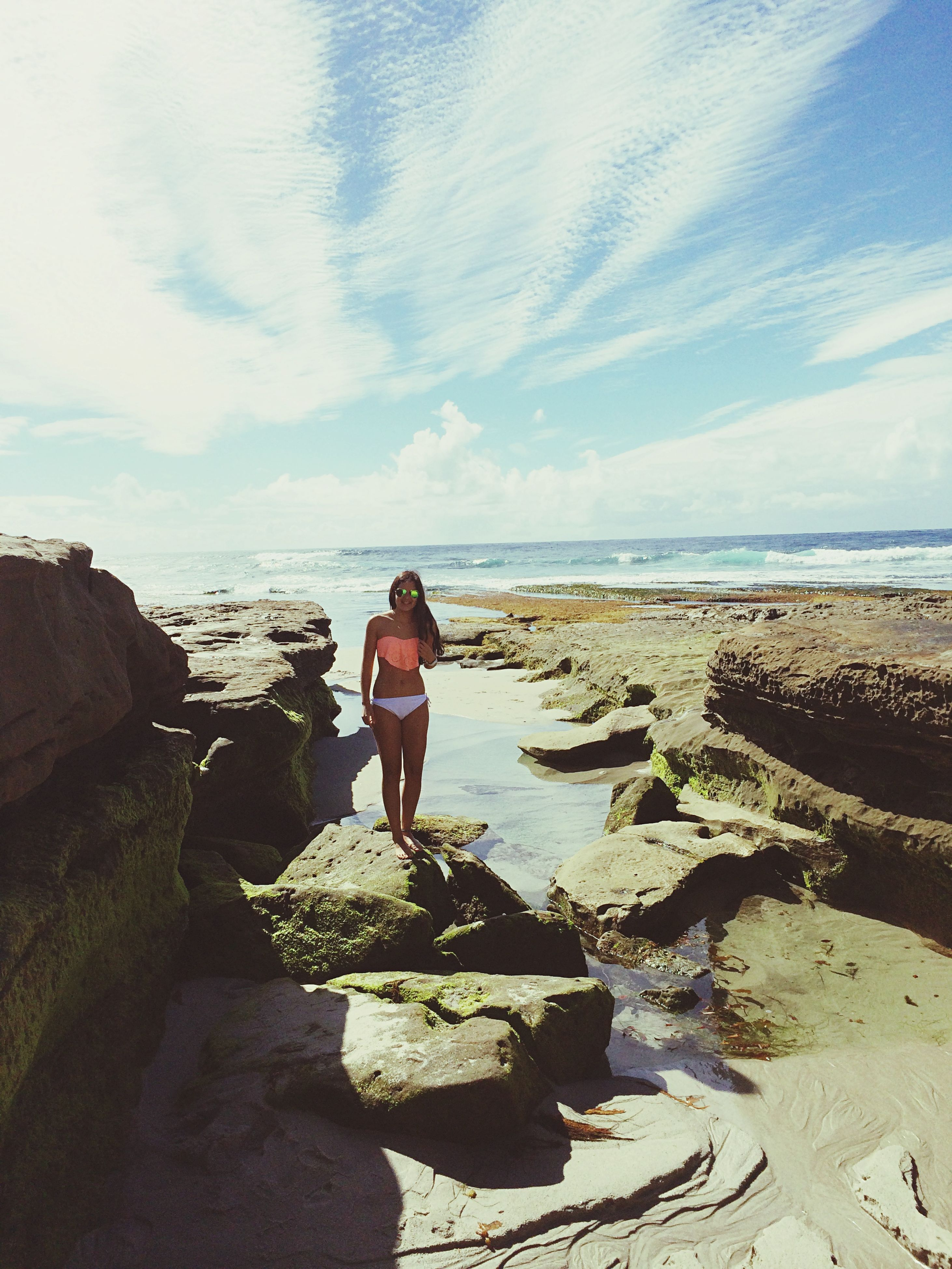 water, sky, sea, lifestyles, horizon over water, leisure activity, beach, rear view, full length, standing, cloud - sky, shore, rock - object, tranquility, casual clothing, nature, scenics, beauty in nature