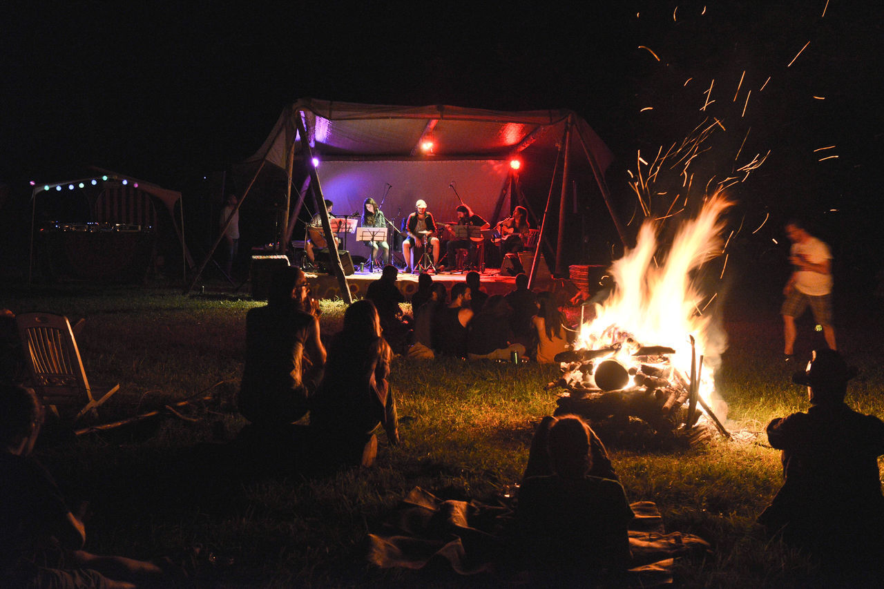 night, burning, illuminated, camping, medium group of people, campfire, real people, flame, women, men, bonfire, outdoors, leisure activity, togetherness, heat - temperature, lifestyles, fire pit, grass, crowd, people