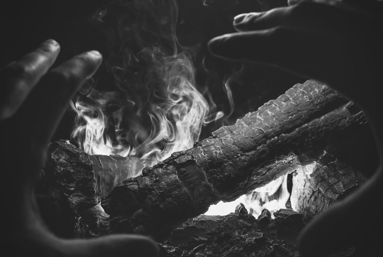 real people, one person, burning, outdoors, human hand, close-up, night, human body part, nature, people