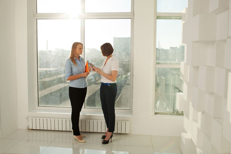 Two elegant businesswomen with tablet and notebook standing at window in office Blonde Businesswomen Caucasian Colleague Electronics  Elegant Female Horizontal Indoors  Looking Office Short Hair Standing Tablet Technology Two Women