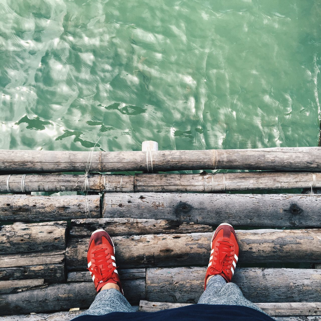 water, low section, human leg, one person, shoe, personal perspective, day, real people, wood - material, standing, leisure activity, outdoors, human body part, lake, red, men, lifestyles, nature, wood paneling, close-up, one man only, people