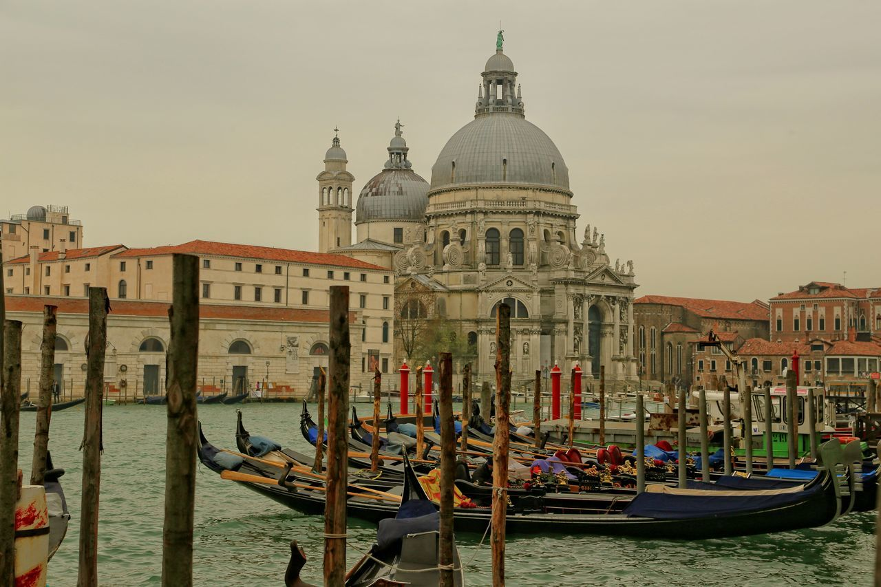 Santa Maria Della Salute By Grand Canal With Gondolas Against Sky In City