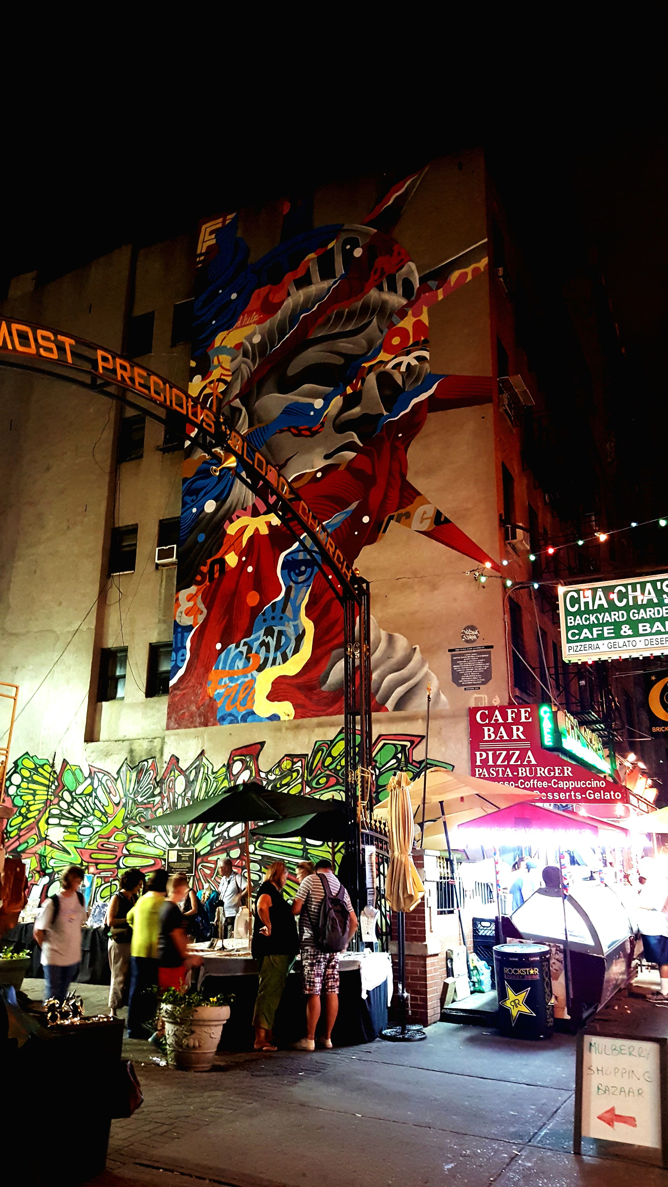 architecture, building exterior, built structure, night, illuminated, city, street, text, graffiti, art, incidental people, outdoors, western script, road, art and craft, communication, multi colored, city life, creativity, low angle view