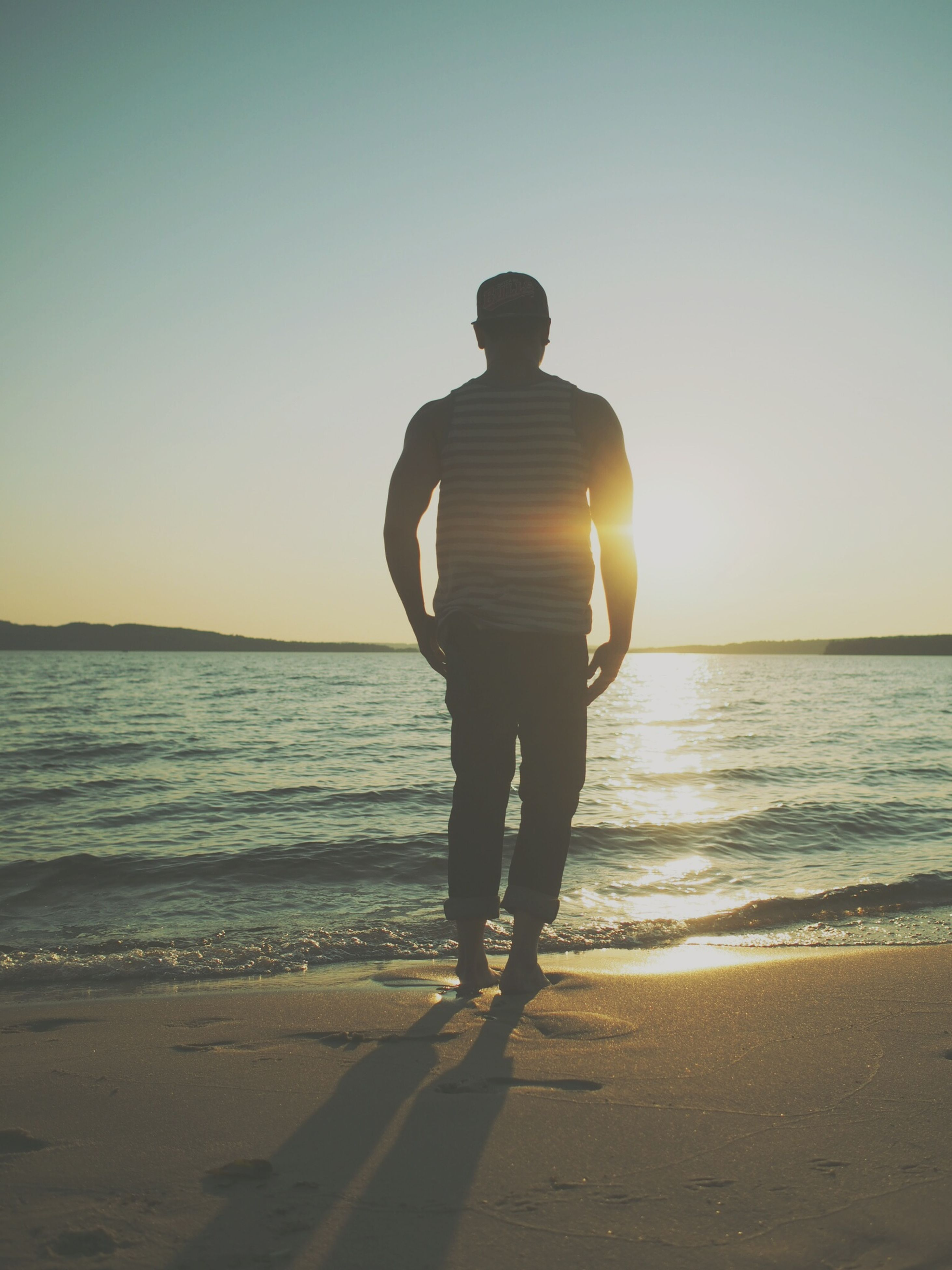 sea, sunset, horizon over water, beach, water, sun, shore, leisure activity, full length, silhouette, lifestyles, standing, clear sky, tranquility, rear view, sunlight, scenics, tranquil scene