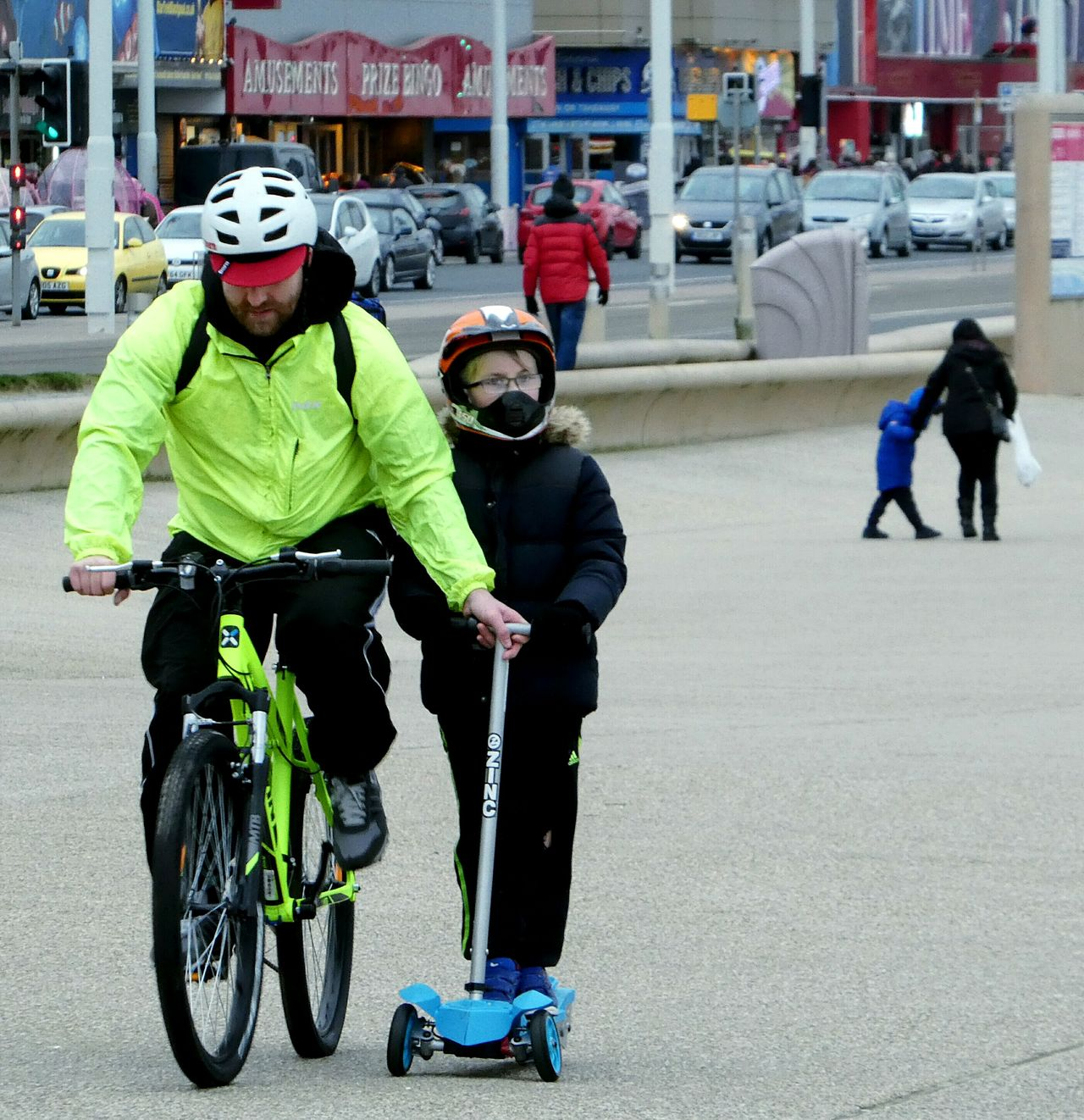 Father and son together against the cold and bitter wind... Headwear Two People Father Son Moments Full Length Cold Temperature Windy Bicycle Scooter Focus On Foreground Helmets Blackpool Promenade