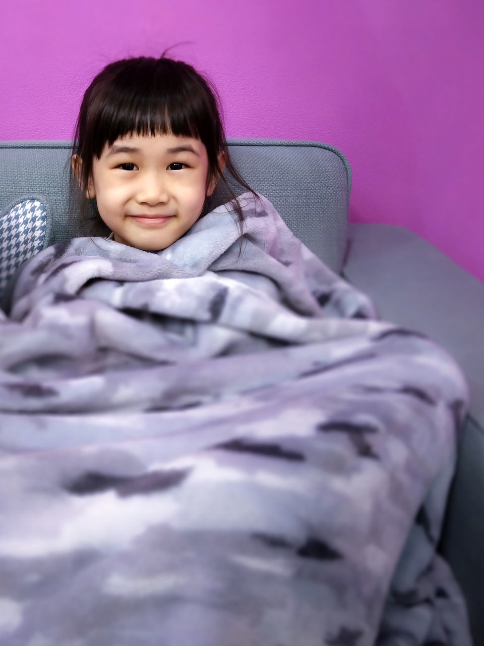 Portrait Of Smiling Girl Covered With Blanket While Sitting On Sofa At Home