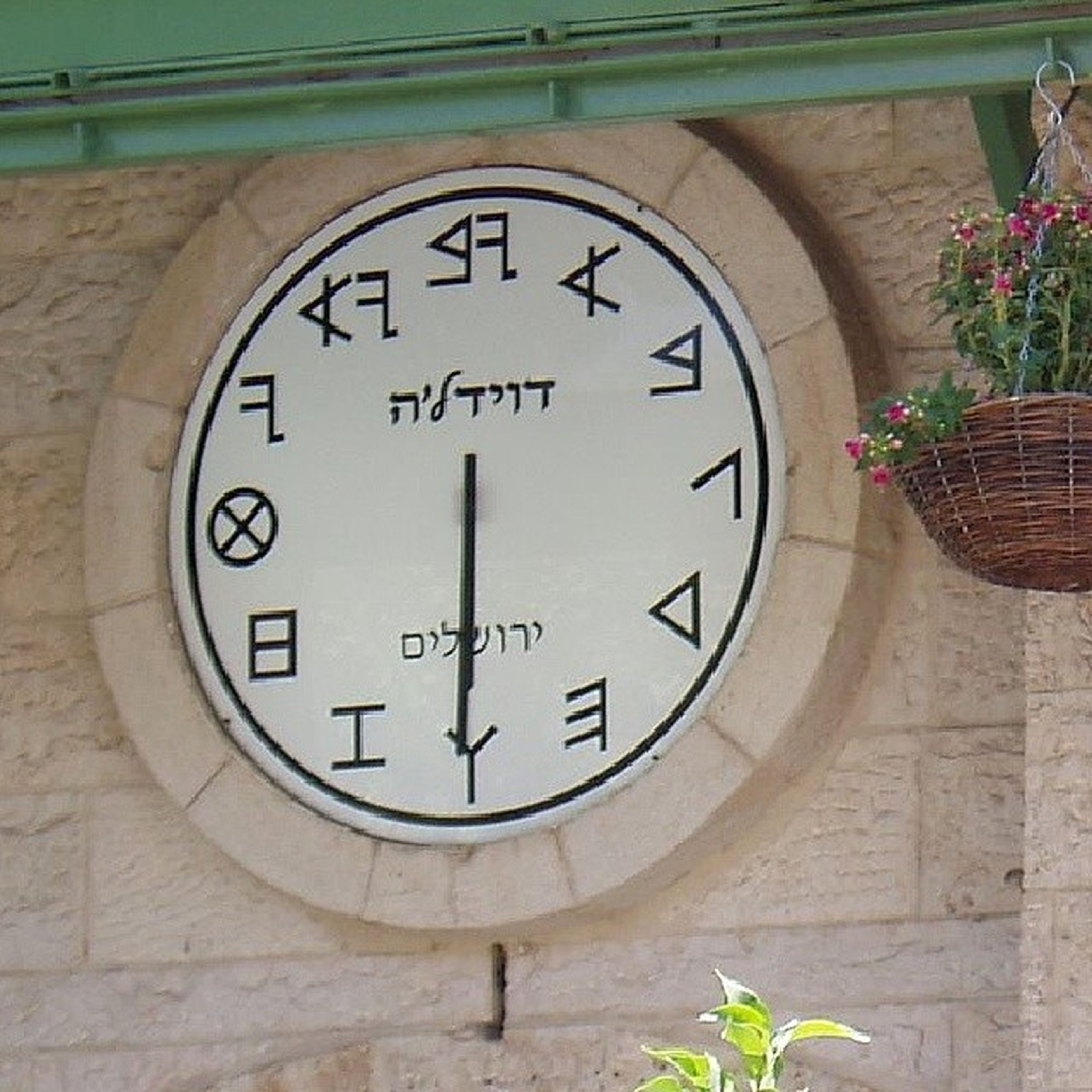 text, communication, western script, plant, clock, flower, time, number, built structure, architecture, close-up, circle, day, no people, wall - building feature, green color, growth, outdoors, leaf, non-western script