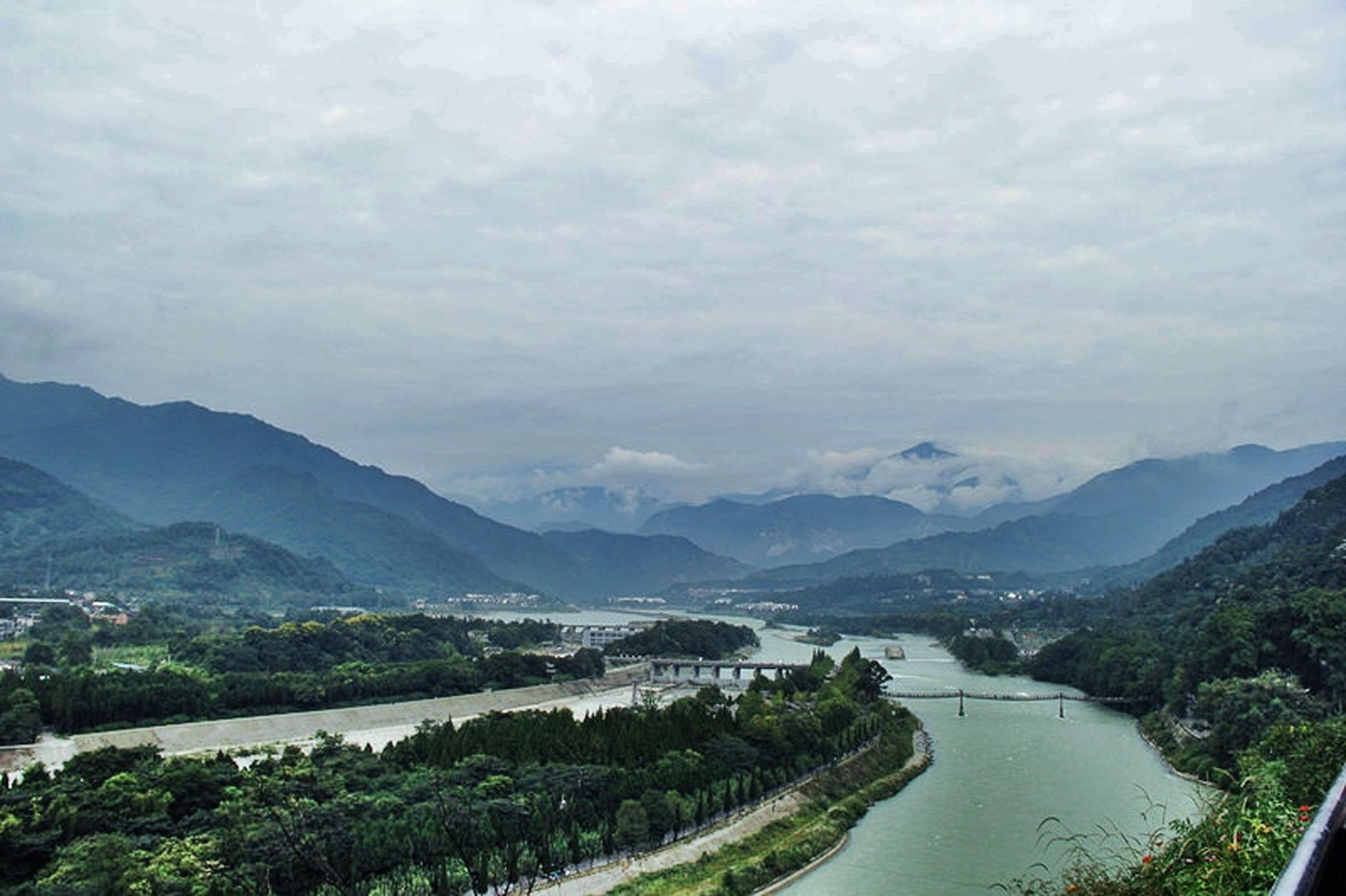 mountain, water, sky, tranquil scene, scenics, mountain range, tranquility, beauty in nature, cloud - sky, nature, lake, cloudy, landscape, river, cloud, tree, idyllic, outdoors, high angle view, sea