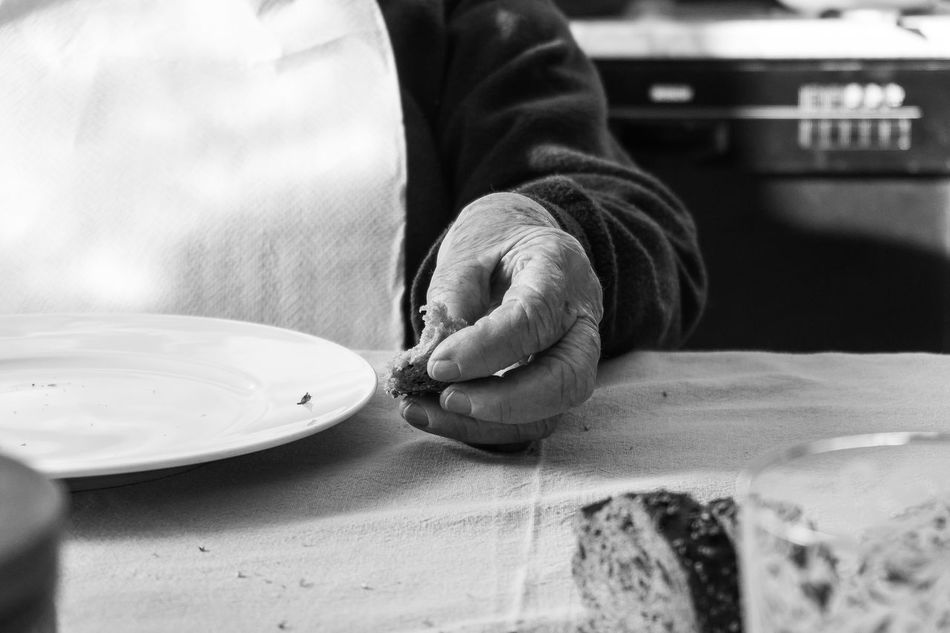 Grandma waiting for lunch, eating bread Adults Only Bnw_captures Bnw_collection Bread Eating Bread Empty Dish Grandma Hand Holding On Human Body Part Human Hand Indoors  Left Hand Midsection One Hand One Person People Real People Sunday Lunch Wrinkled Hand Wrinkled Skin