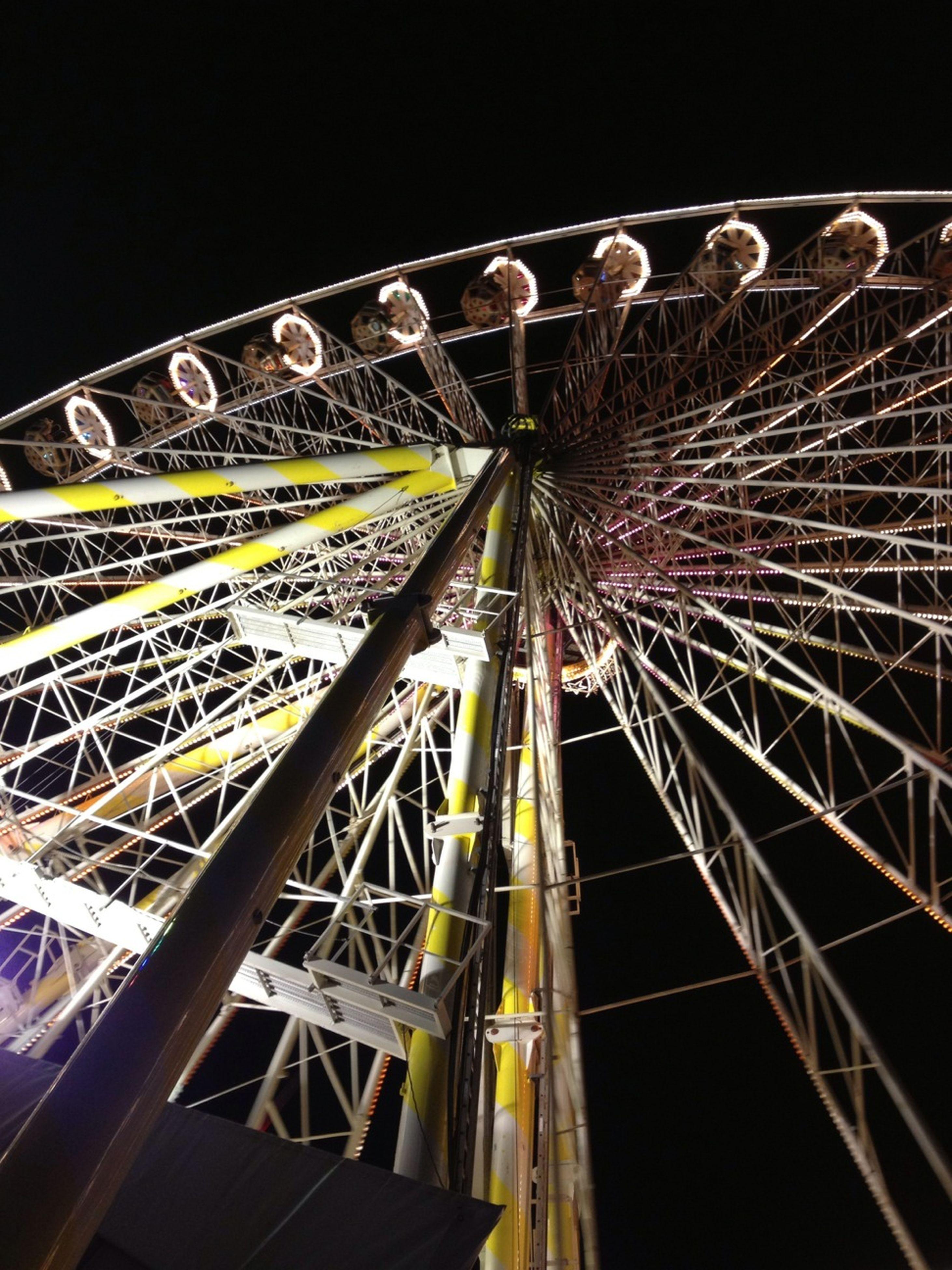 arts culture and entertainment, amusement park, amusement park ride, ferris wheel, night, low angle view, illuminated, built structure, clear sky, architecture, sky, motion, fun, long exposure, outdoors, leisure activity, large, enjoyment, traveling carnival, fairground ride