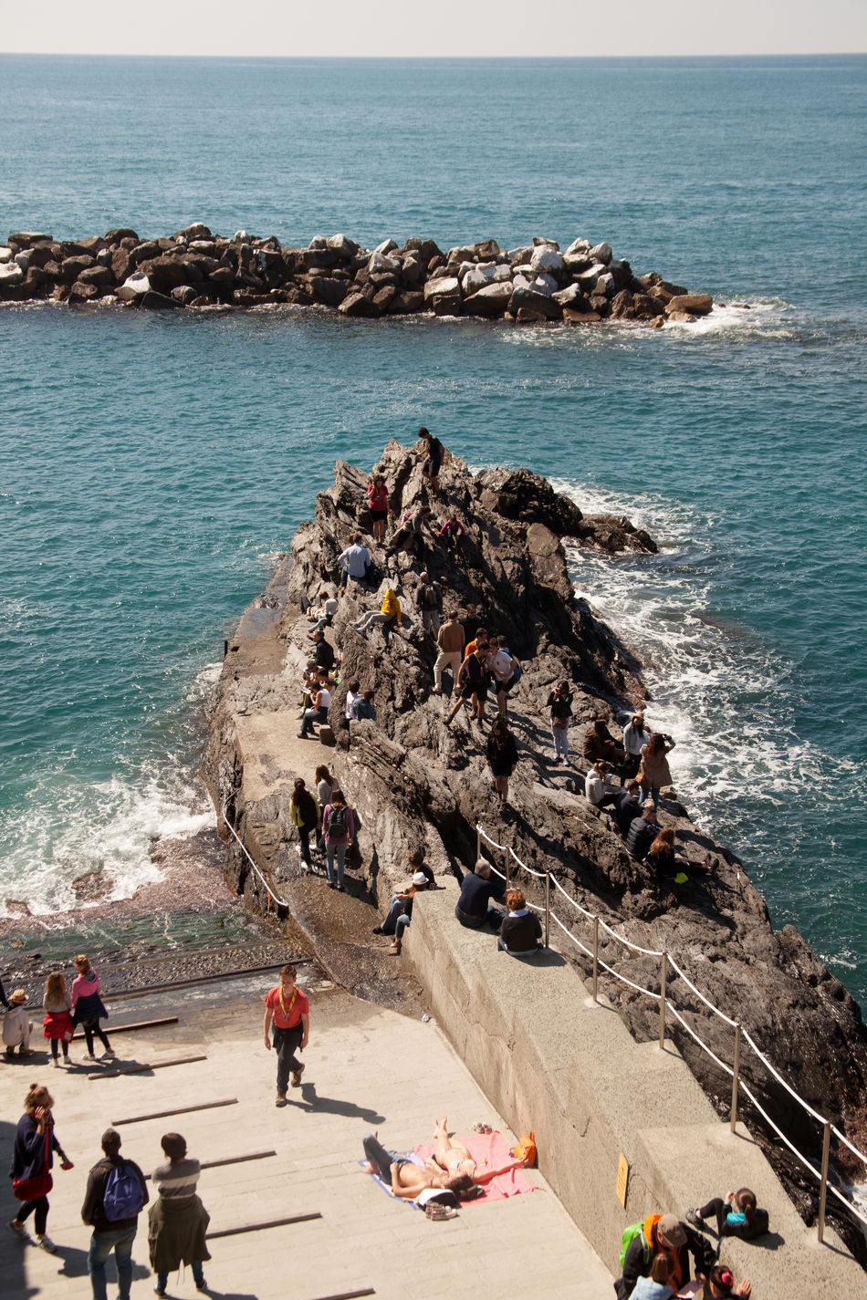 People on the rocks in Manarola, Cinque Terre, Italy Beauty In Nature Boat Cinque Terre Cinqueterre Coast Day Docks Horizon Over Water Nature People Seating Pier Rock - Object Rock Formation Scenics Sea Ship Shipping  Sky Tranquil Scene Tranquility Traveling Water