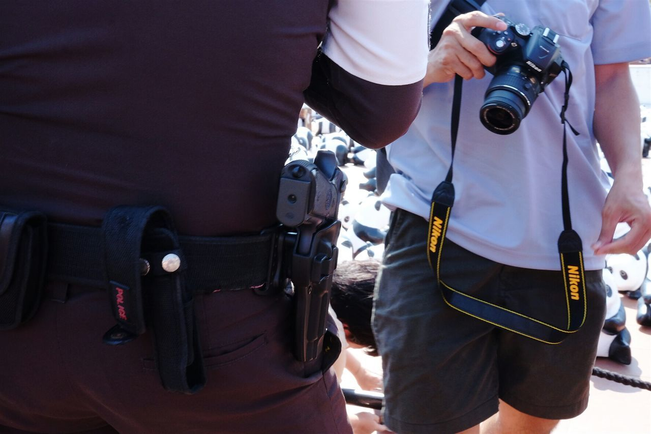 uniform, police force, protection, weapon, midsection, gun, men, safety, authority, standing, real people, occupation, military uniform, police uniform, government, camera - photographic equipment, protective workwear, day, walkie-talkie, outdoors, military, working, people