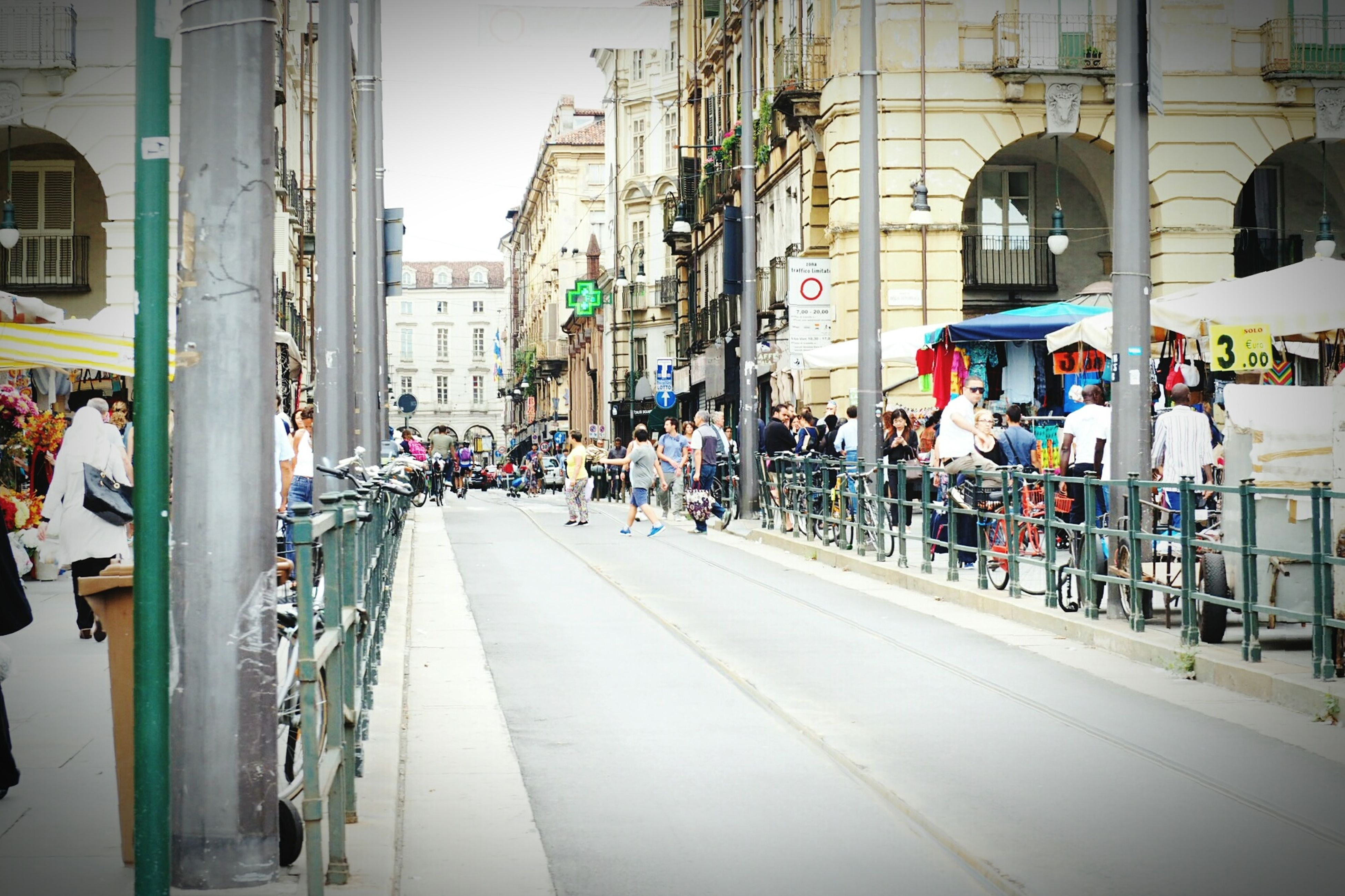 built structure, architecture, building exterior, city, street, road, transportation, city street, men, large group of people, car, city life, land vehicle, travel destinations, outdoors, day, pedestrian, surface level