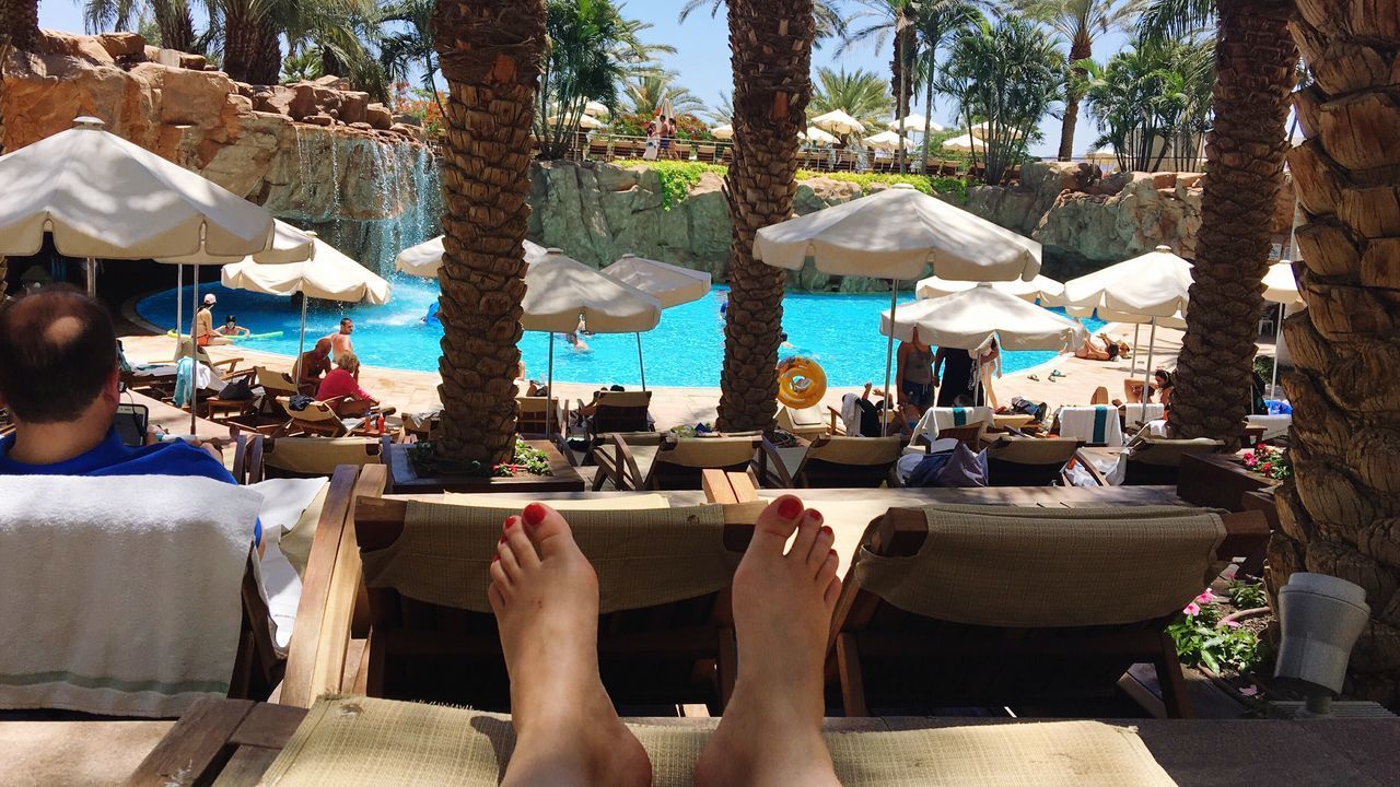 Vacations Swimming Pool Real People Swimming Women Relaxation Outdoors Pool Table Leisure Activity Tourist Resort Lifestyles One Person Adults Only Sitting Low Section People Tree Adult Men Eilat Israel Barefoot Vacation Poolside Live For The Story