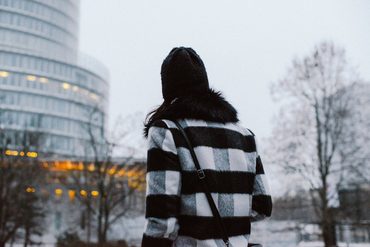 Building Exterior City City Cold Cold Temperature Colors Day Fashion Lifestyles Lights One Person Outdoors Portrait Real People Rear View Sky Snow Squares Tree Winter Uniqueness