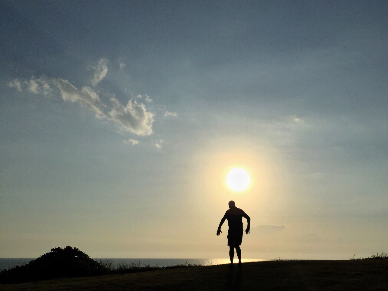 Silhouette Man Standing On Hill In Front Of Sea At Sunset
