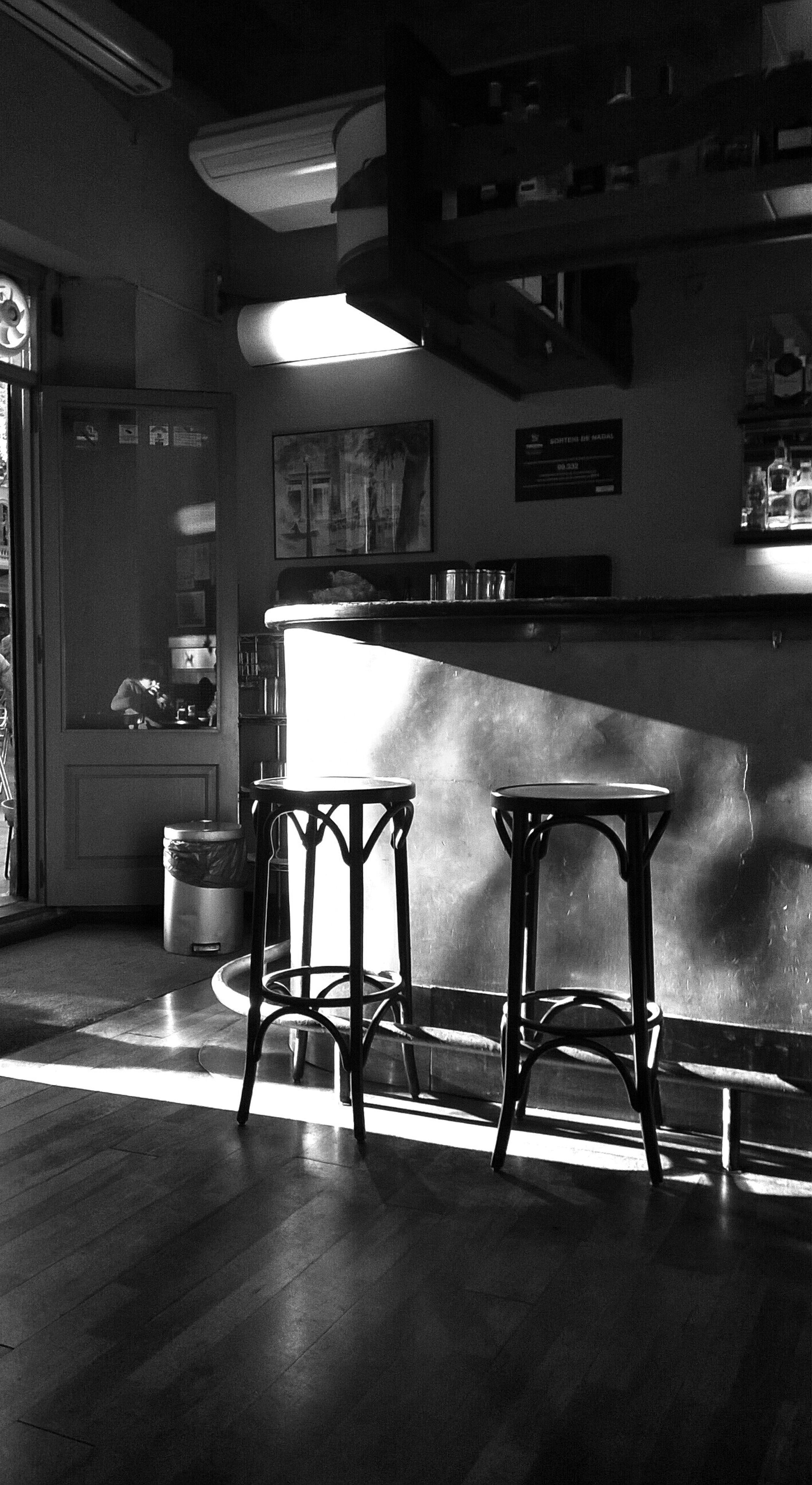 indoors, chair, empty, absence, seat, table, architecture, built structure, illuminated, flooring, restaurant, furniture, interior, window, no people, lighting equipment, tiled floor, sunlight, door, day