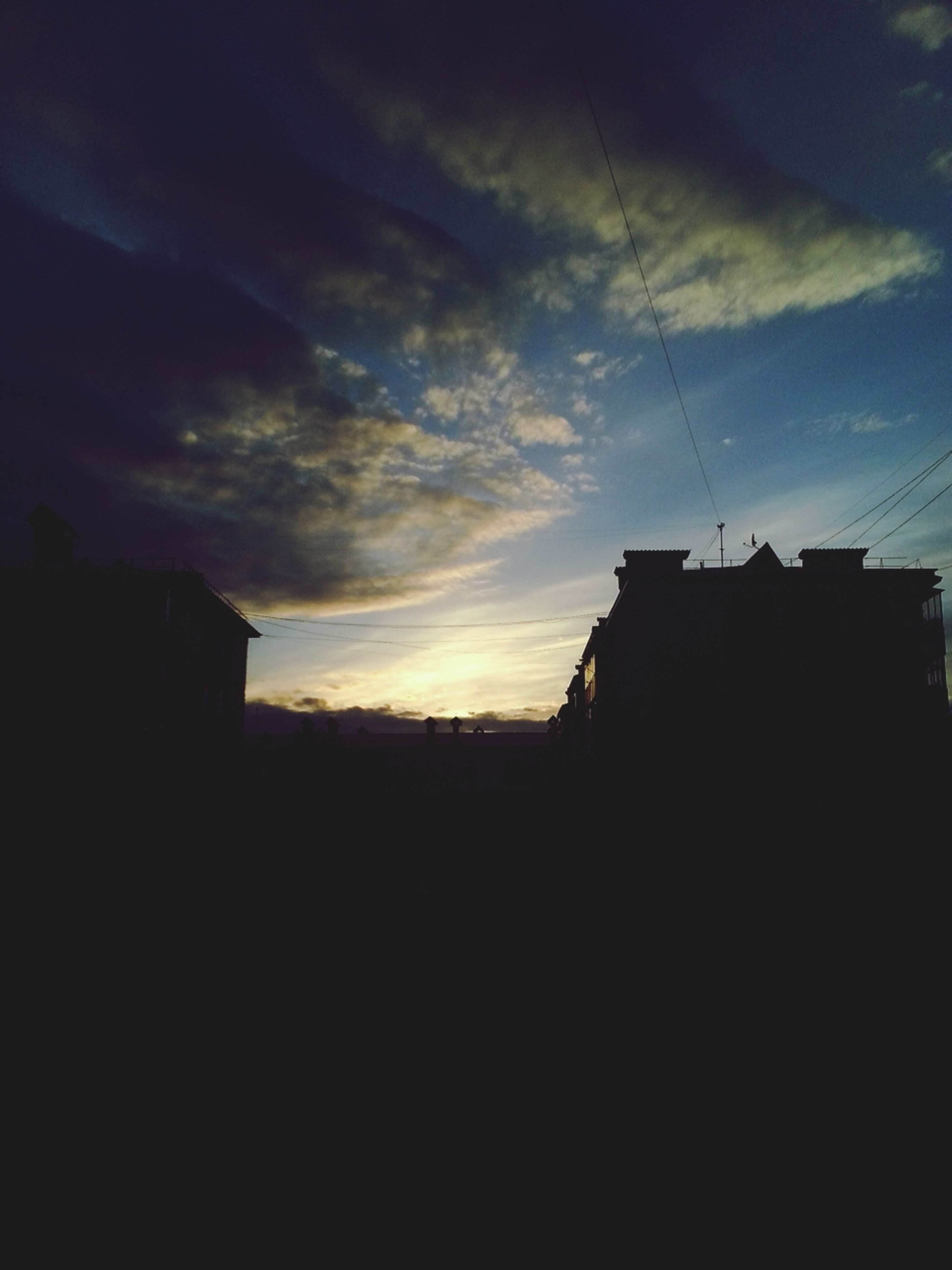 architecture, silhouette, building exterior, built structure, sky, sunset, cloud - sky, house, residential structure, cloud, dark, cloudy, building, dusk, residential building, low angle view, outdoors, nature, no people, dramatic sky