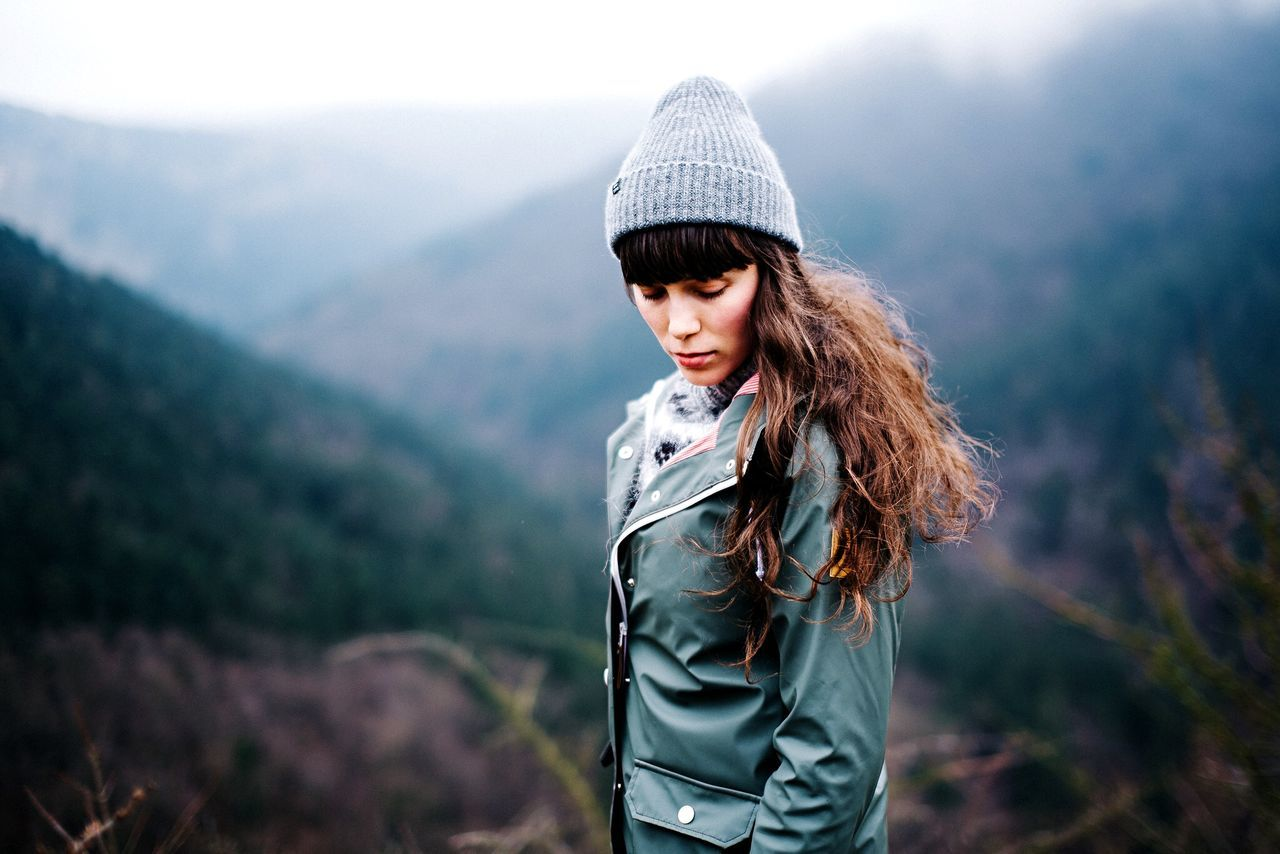mountain, real people, nature, focus on foreground, one person, casual clothing, young adult, beauty in nature, standing, outdoors, landscape, day, mountain range, young women, looking at camera, lifestyles, portrait, tree, scenics, close-up, people