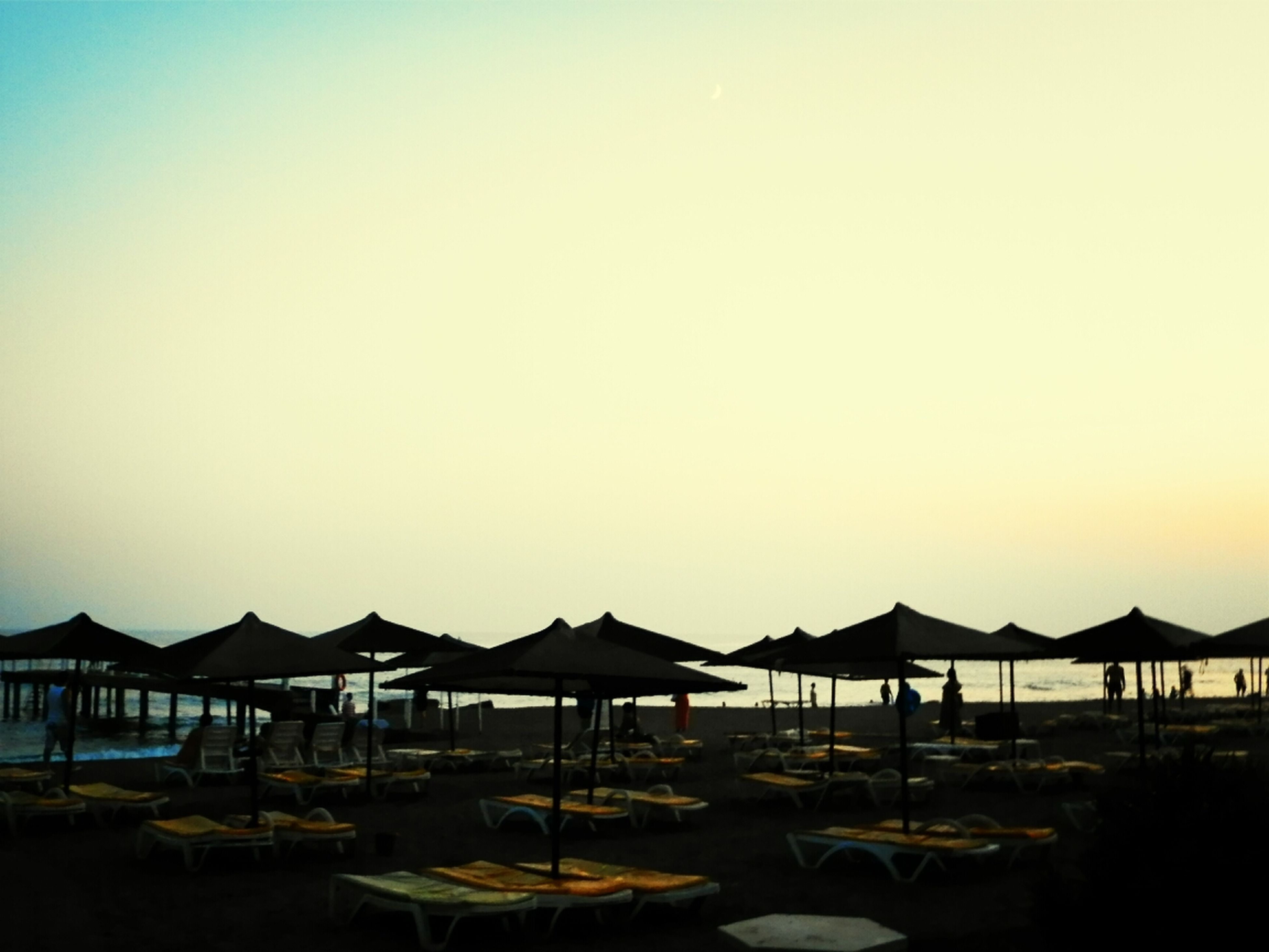 clear sky, copy space, water, sea, tranquil scene, beach, tranquility, chair, built structure, horizon over water, scenics, nature, incidental people, parasol, beauty in nature, sunshade, empty, architecture, pier, outdoors
