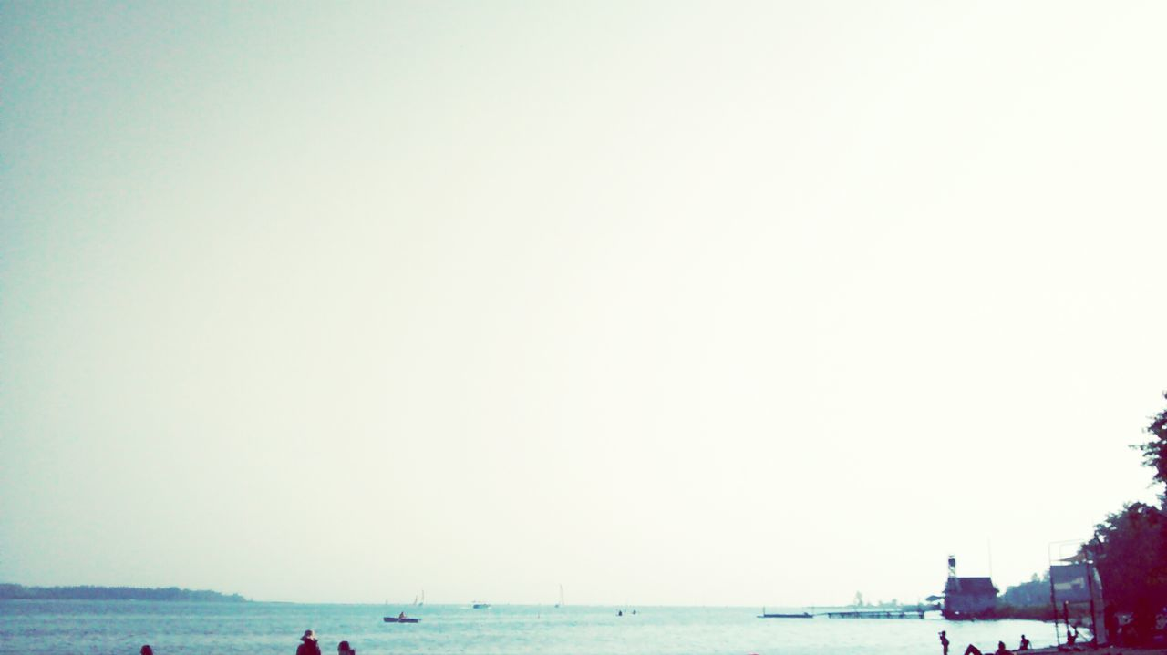 sea, copy space, water, incidental people, beach, clear sky, outdoors, nature, horizon over water, vacations, travel destinations, tourism, beauty in nature, scenics, day, sky, building exterior, large group of people, architecture, nautical vessel, city, people