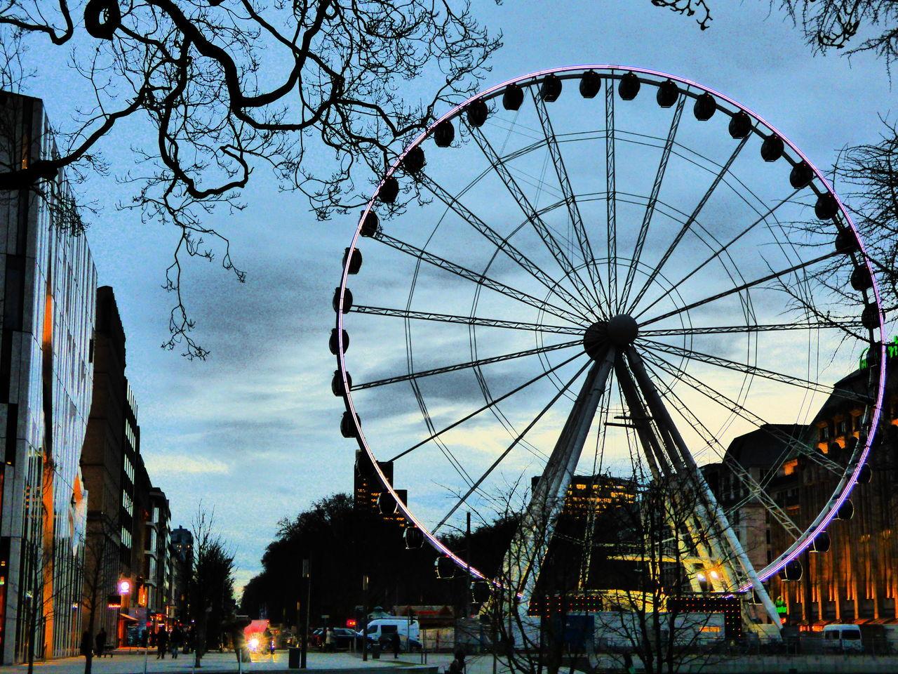 ferris wheel, amusement park, arts culture and entertainment, big wheel, sky, amusement park ride, built structure, tree, outdoors, architecture, building exterior, no people, low angle view, day, clear sky, city
