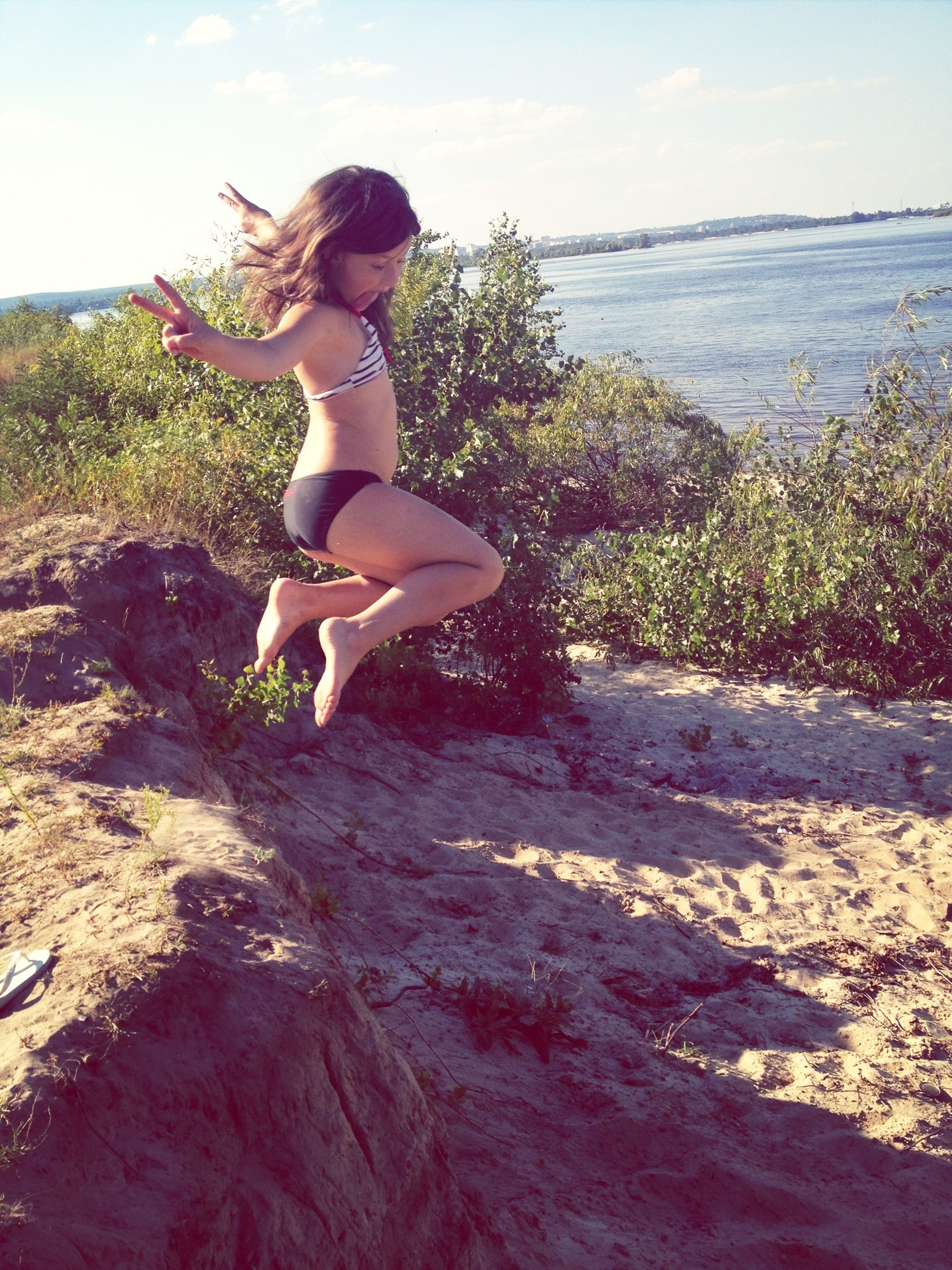 full length, lifestyles, young adult, leisure activity, young women, person, casual clothing, sky, jumping, arms outstretched, mid-air, carefree, side view, standing, enjoyment, fun, water, beach