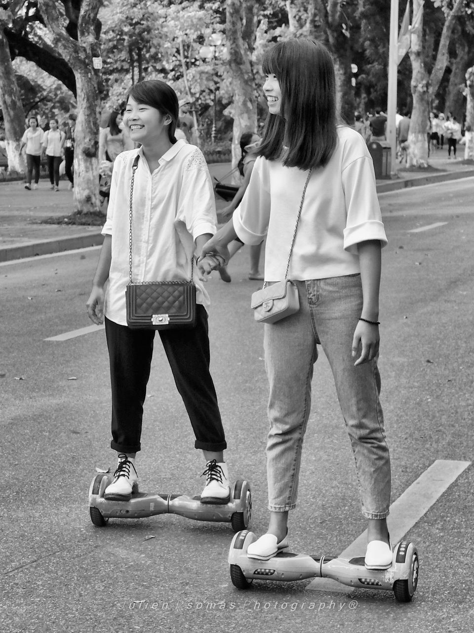 full length, leisure activity, casual clothing, real people, standing, two people, lifestyles, skateboard, girls, togetherness, outdoors, day, childhood, playing, fun, boys, happiness, tree, smiling, friendship, young adult, people
