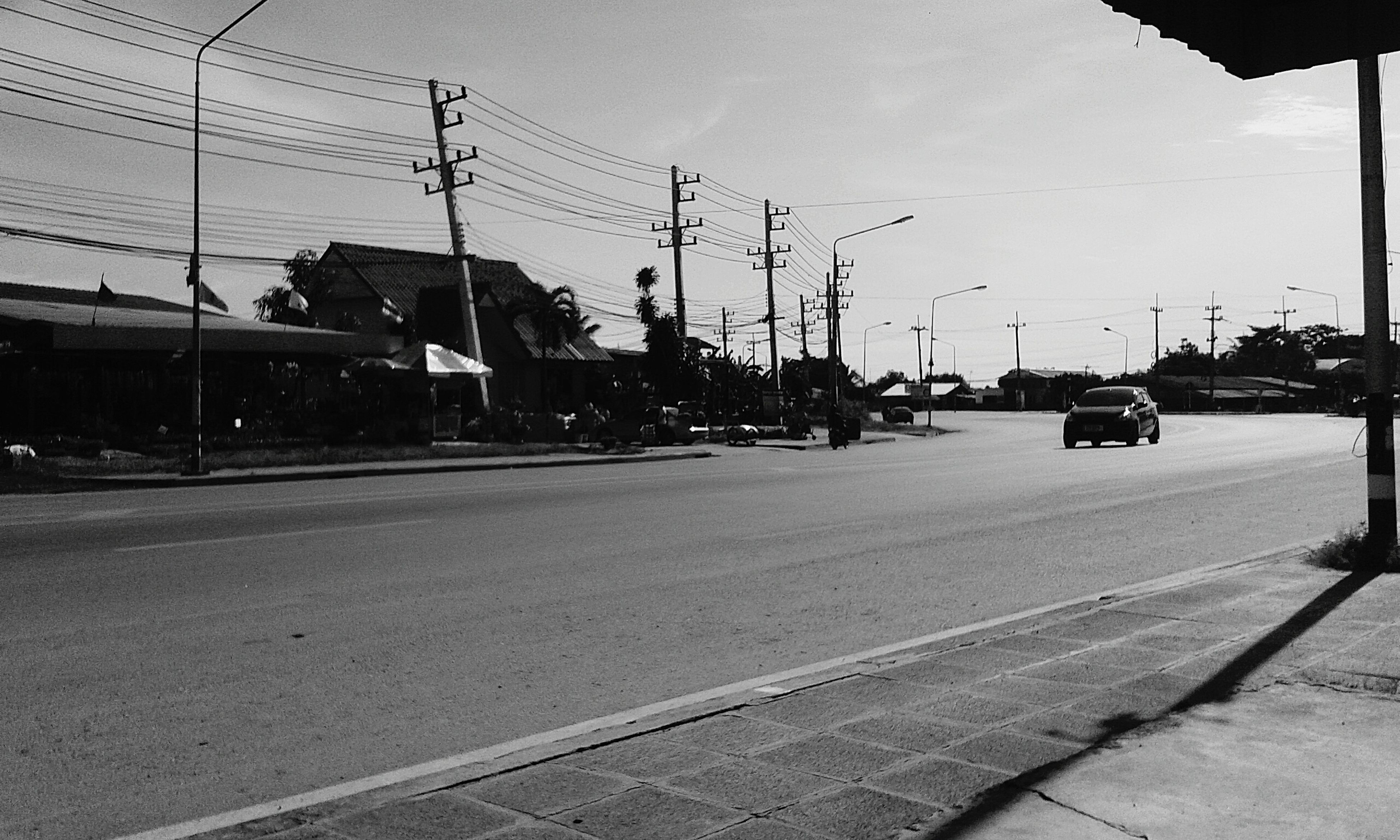 transportation, street, power line, car, mode of transport, building exterior, land vehicle, road, sky, electricity pylon, city, built structure, railroad track, architecture, street light, the way forward, city street, road marking, city life, outdoors