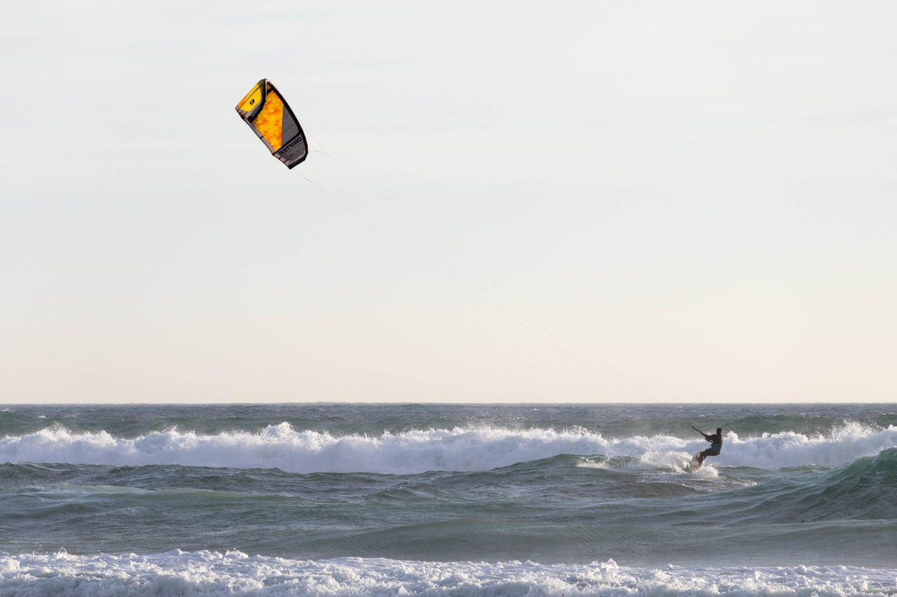 Mid Distance View Of Silhouette Person Kitesurfing On Sea