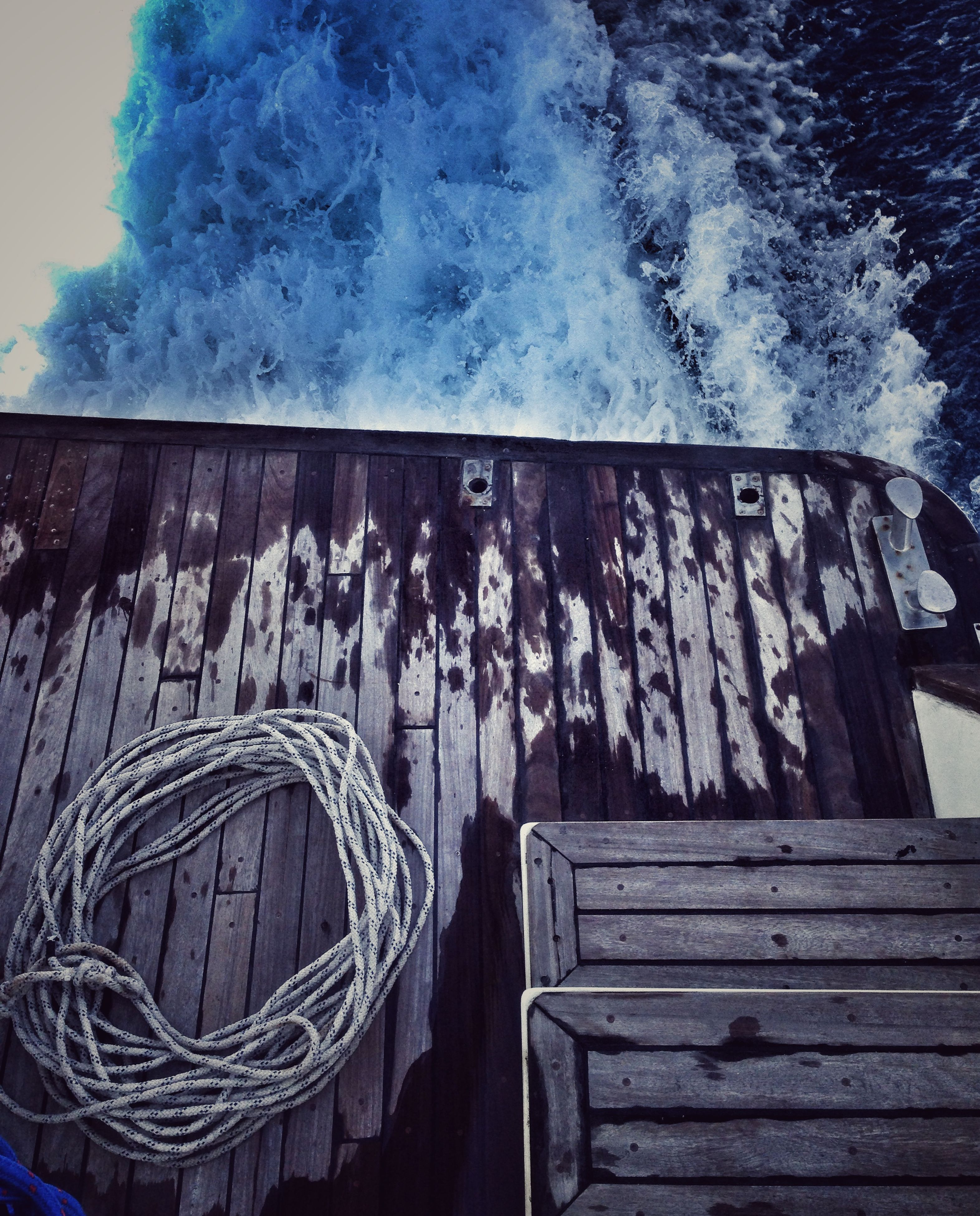 wood - material, wooden, text, built structure, day, wood, close-up, building exterior, outdoors, no people, architecture, western script, blue, water, sunlight, nature, house, art and craft, creativity, communication